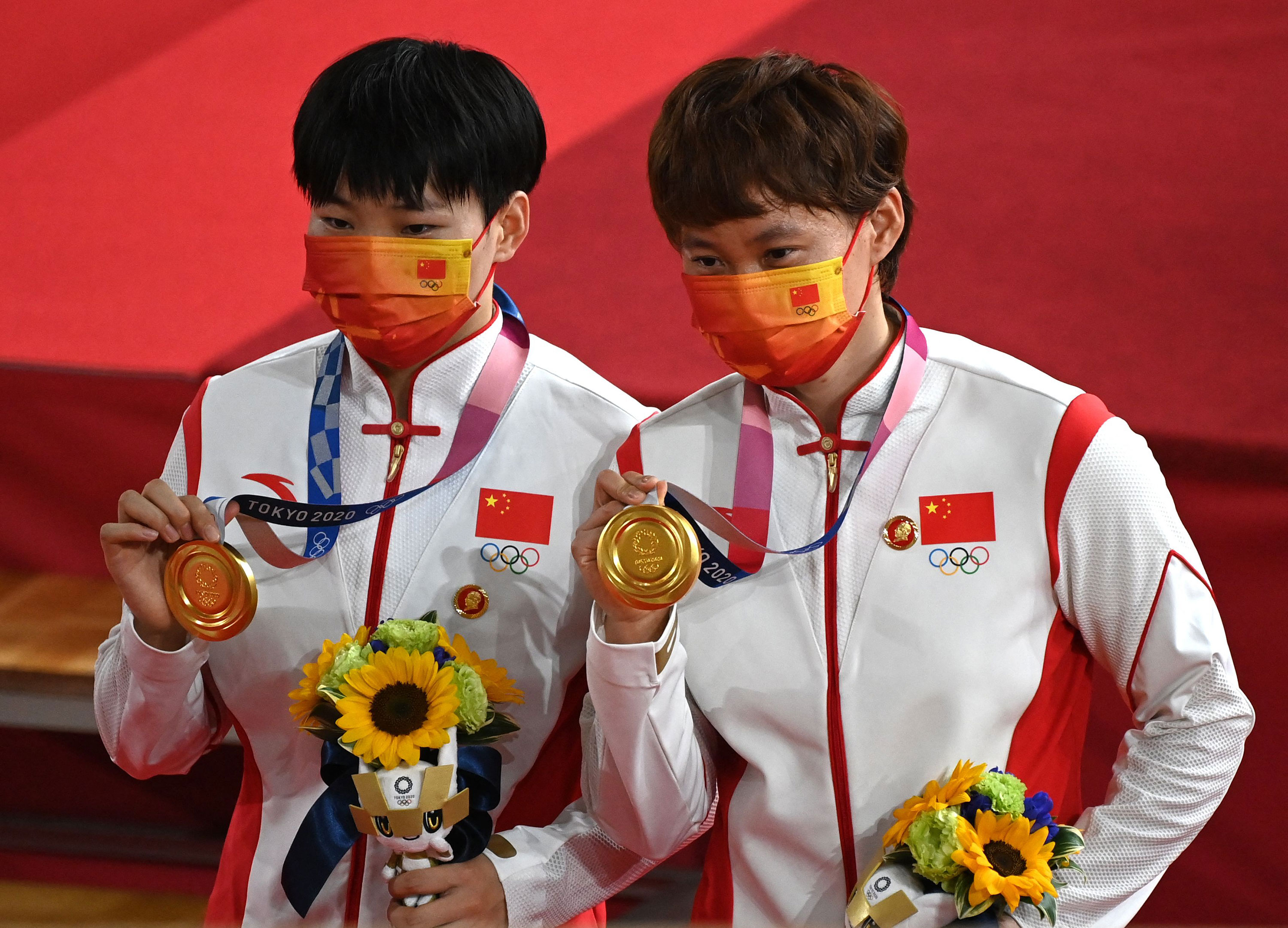 China's Bao Shanju, left, and Zhong Tianshi pose with their gold medals on the podium after the track cycling team sprint final on August 2.
