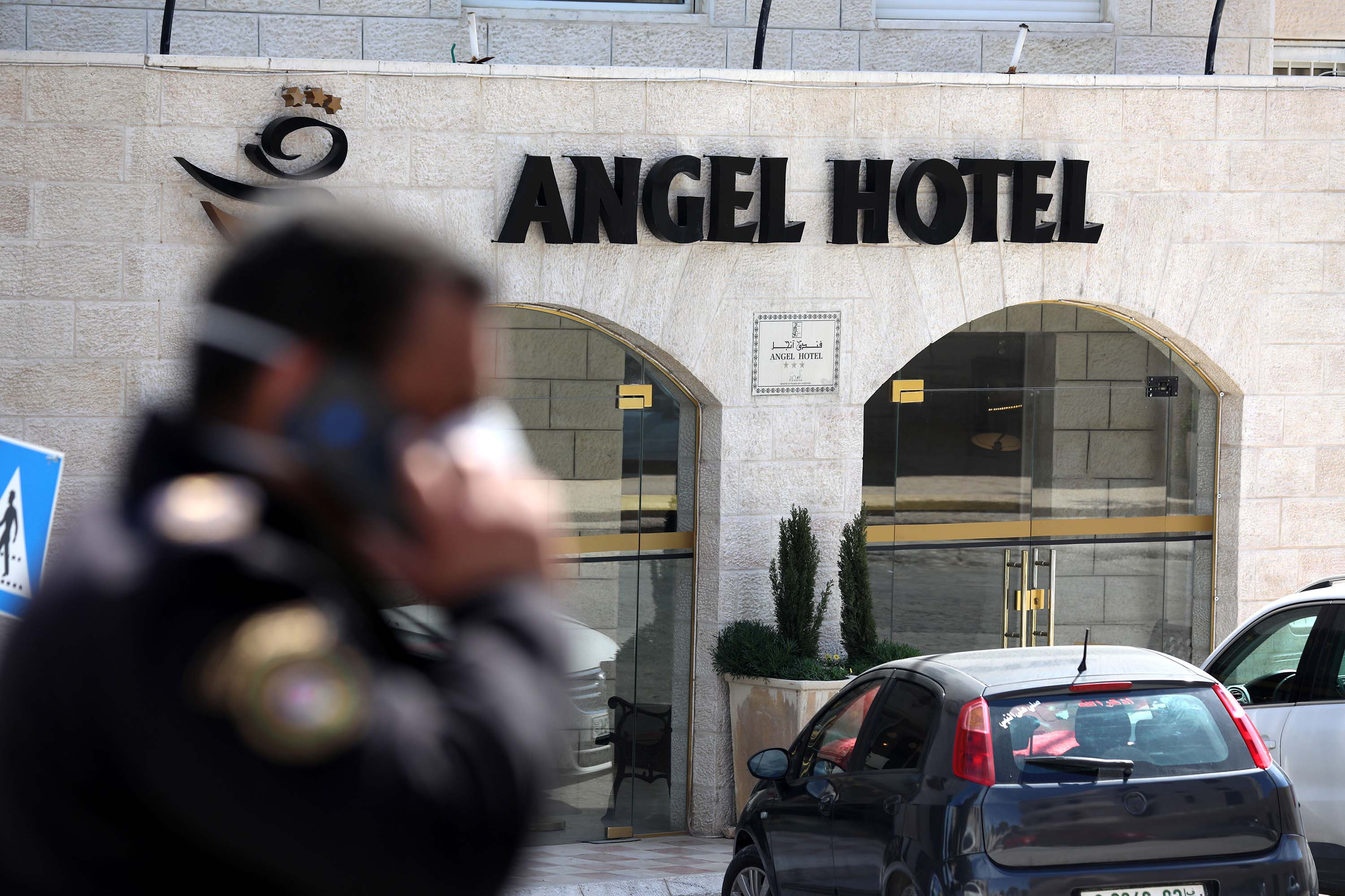 A police officer stands guard outside a quarantined hotel in Bethlehem, West Bank on Friday.