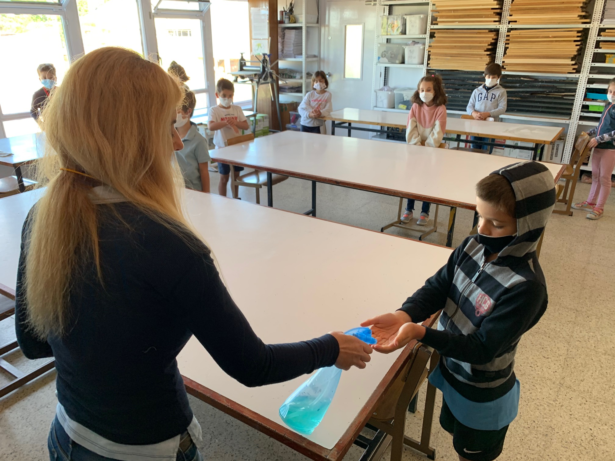 A teacher offers hand-sanitizing gel to a student at Colegio Virgen de Europa in Madrid, on Friday, June 12. Students have to disinfect their hands before and after each class.