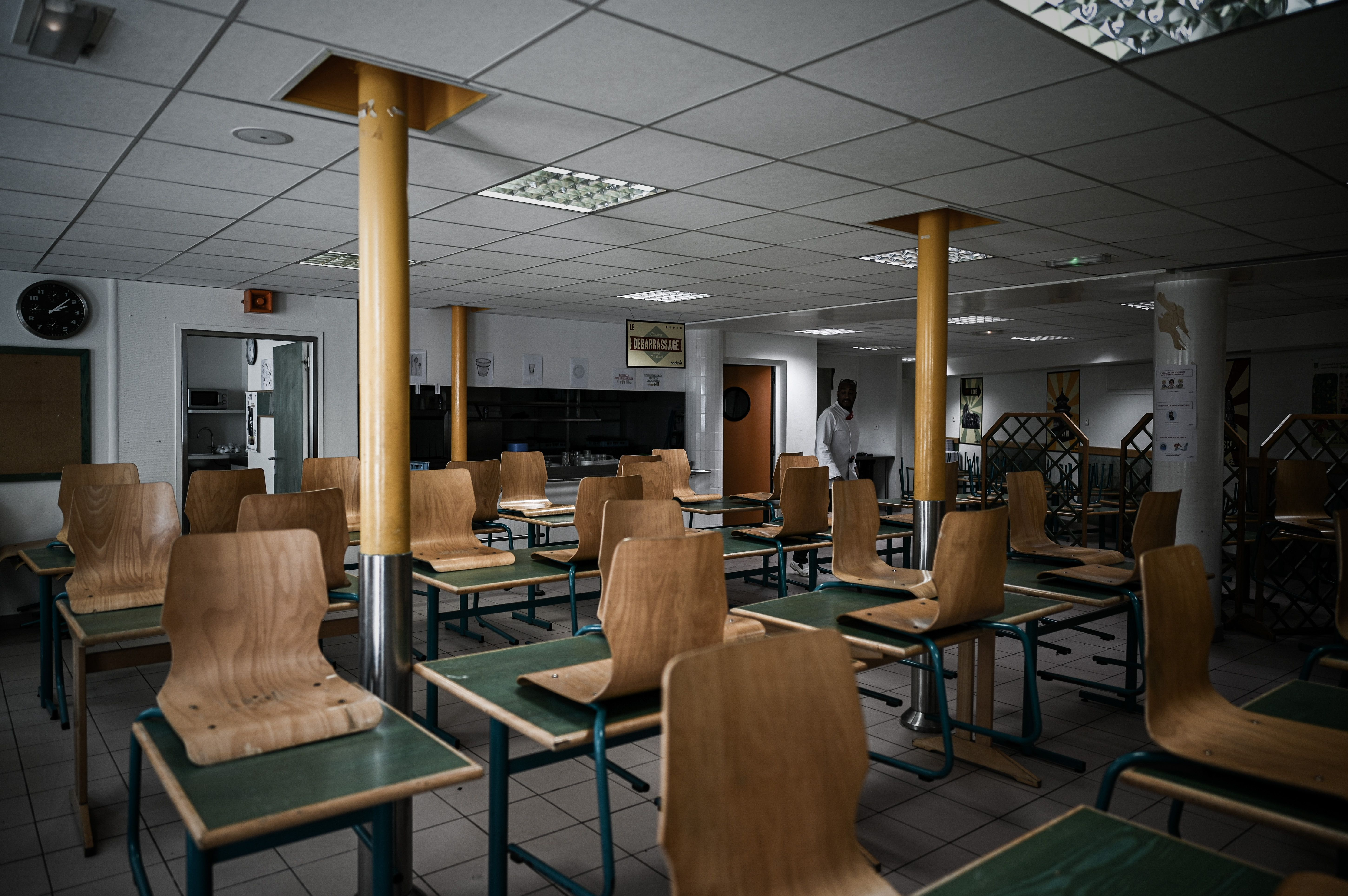 A staff member walks in the canteen of the private school Institut Sainte Genevieve prepared to respecting the social distance with only two children per table, in the French capital Paris on May 7, 2020, as the schools in France are to gradually reopen from May 11, when a partial lifting of restrictions due to the Covid-19 pandemic caused by the novel coronavirus will come into effect. (Photo by PHILIPPE LOPEZ / AFP) (Photo by PHILIPPE LOPEZ/AFP via Getty Images)