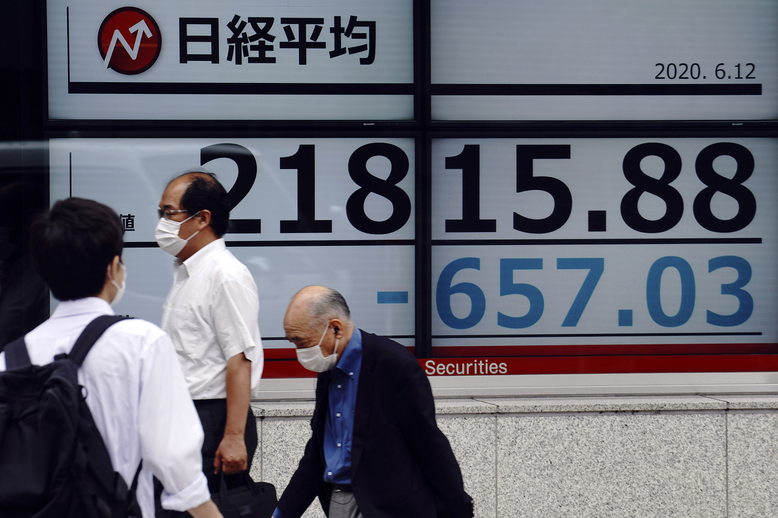 People walk past an electronic stock board showing Japan's Nikkei 225 index at a securities firm in Tokyo, Japan, on Friday, June 12.