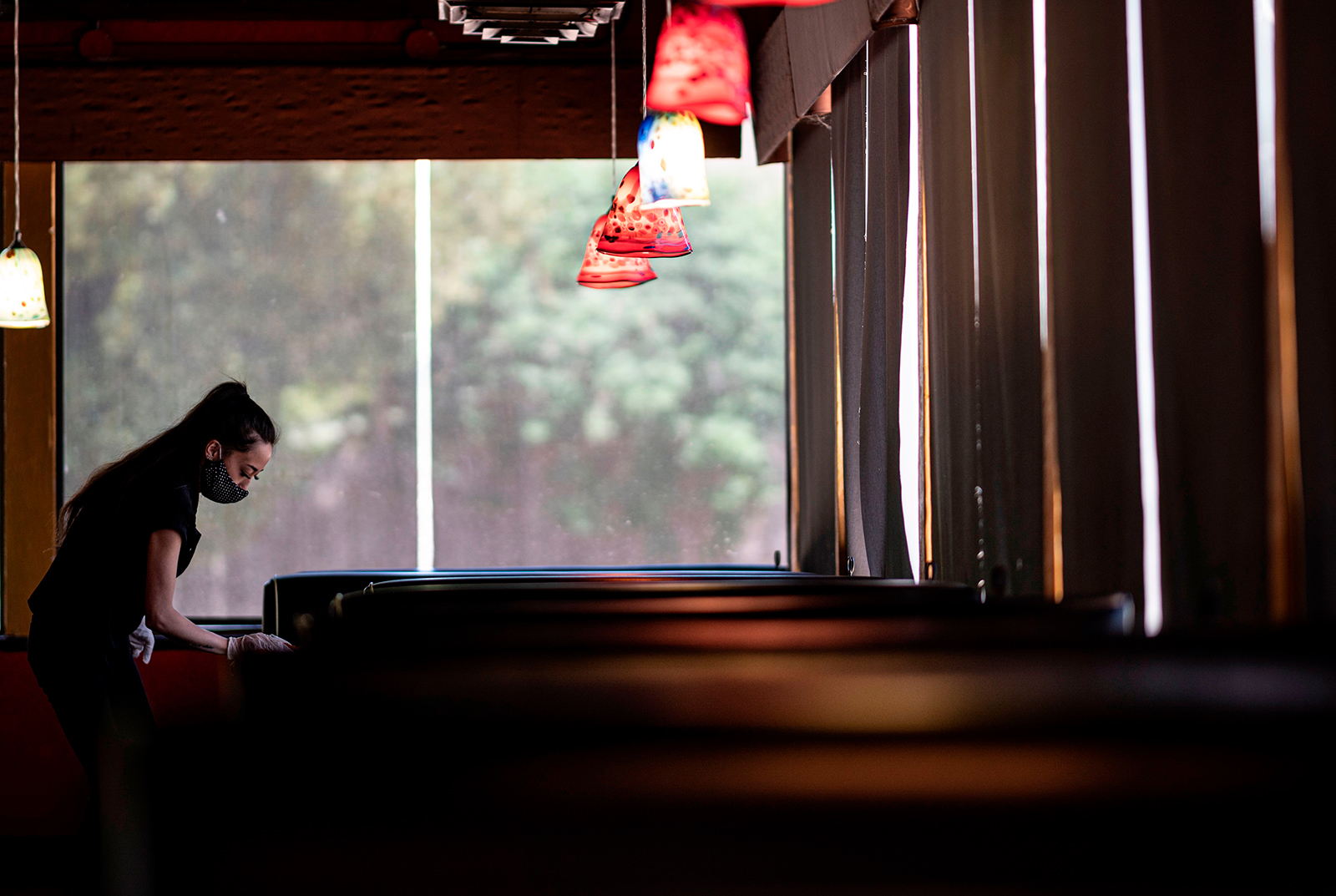 A waitress wearing a mask and gloves disinfects a table in a Restaurant on May 5, in Stillwater, Oklahoma.