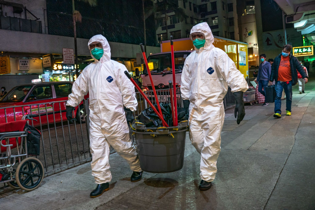 Workers wearing personal equipment carry cleaning supplies into a residential building at North Point district on February 23 in Hong Kong.