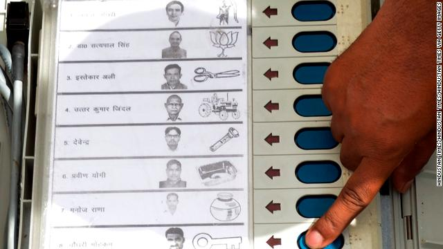 An electronic voting machine shows party symbols alongside candidates' names.