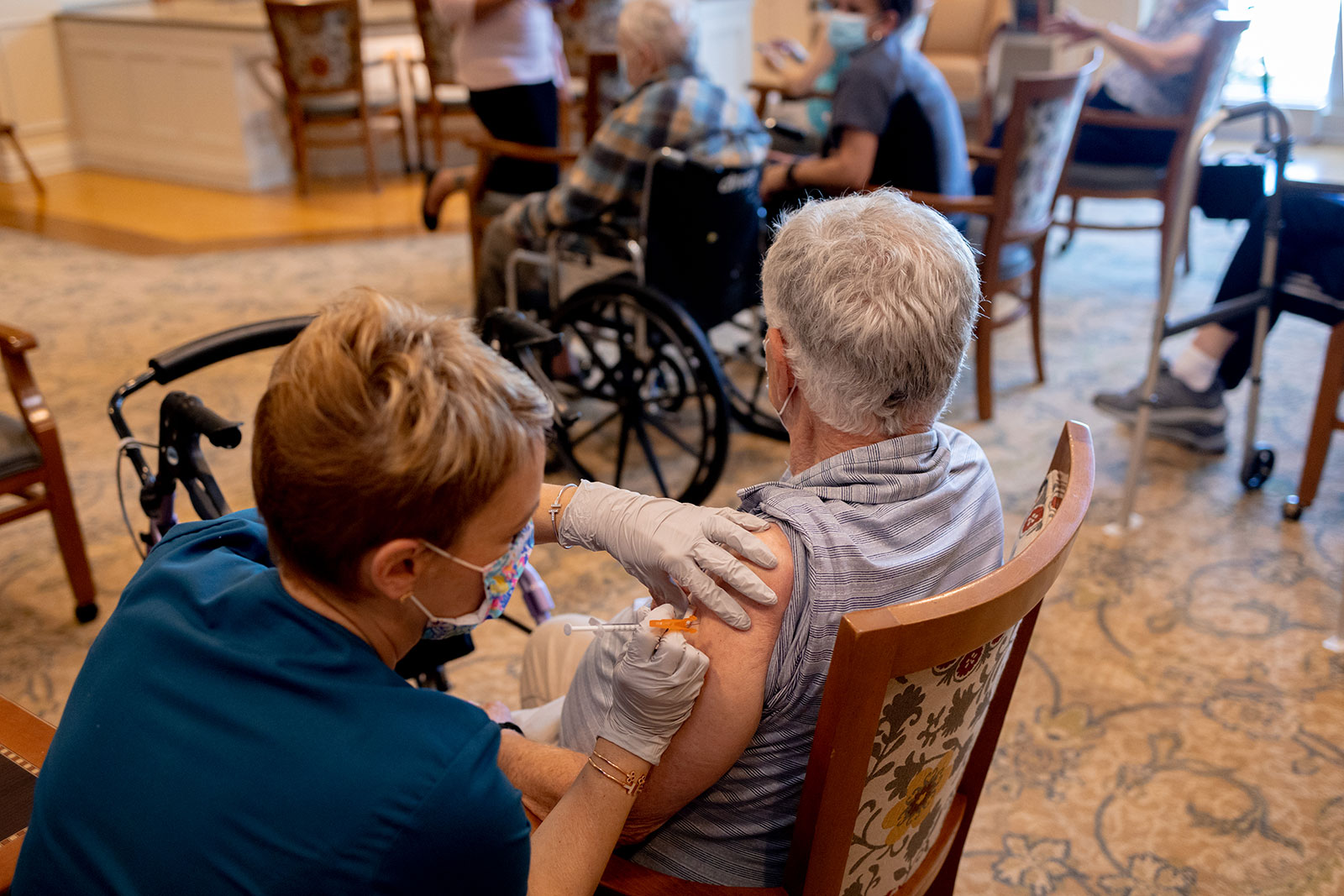 A healthcare worker administers a Covid-19 booster shot at a senior living facility in Worcester, Pennsylvania.