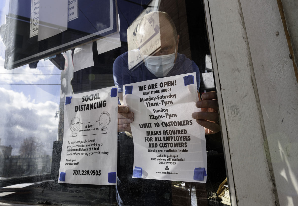A worker places signs informing customers and employees to wear masks and socially distance outside a store in downtown Fargo, North Dakota on October 14.