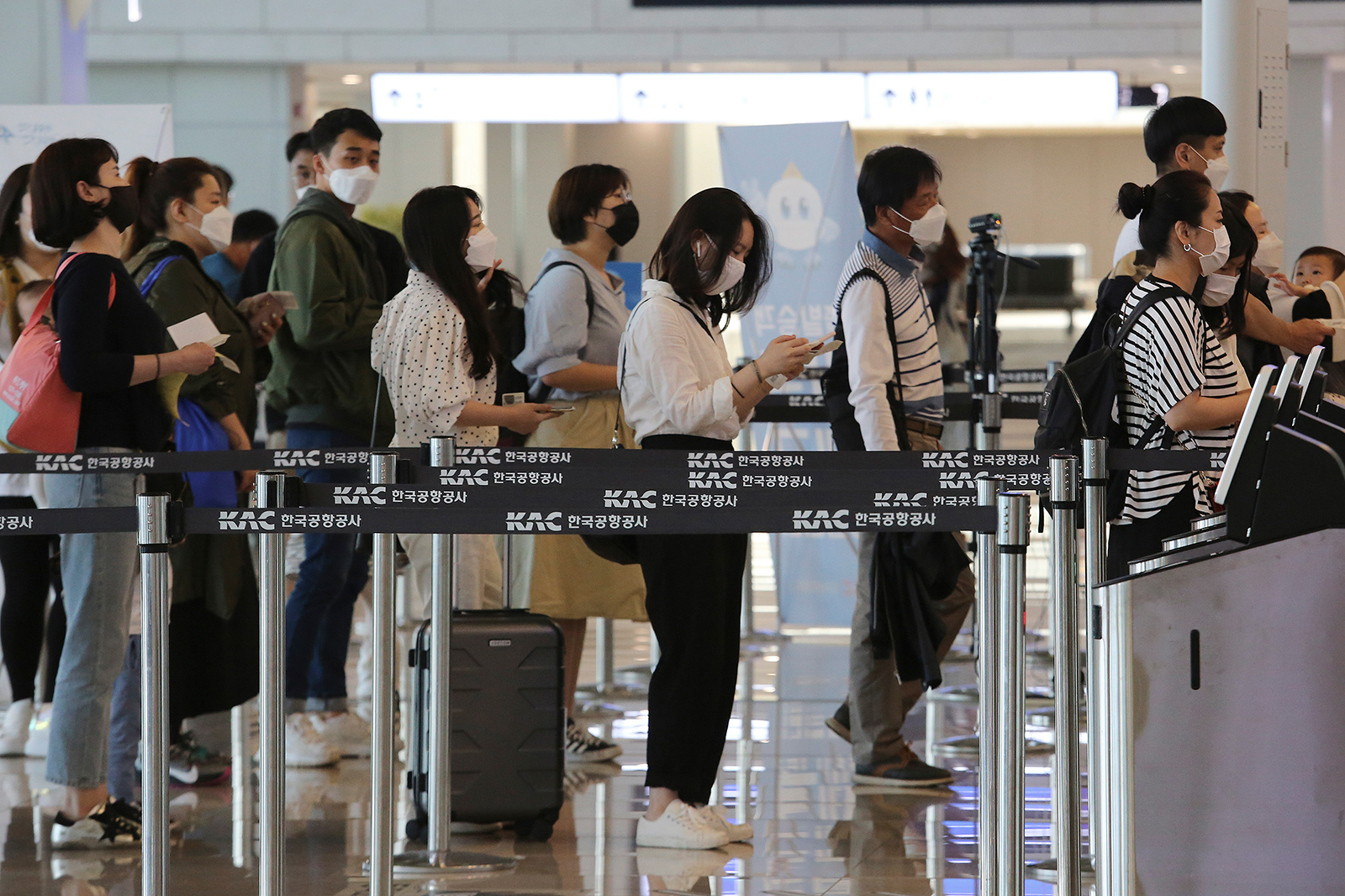 Passengers wearing face masks line up to board their planes at the domestic flight terminal of Gimpo Airport in Seoul, on May 27.