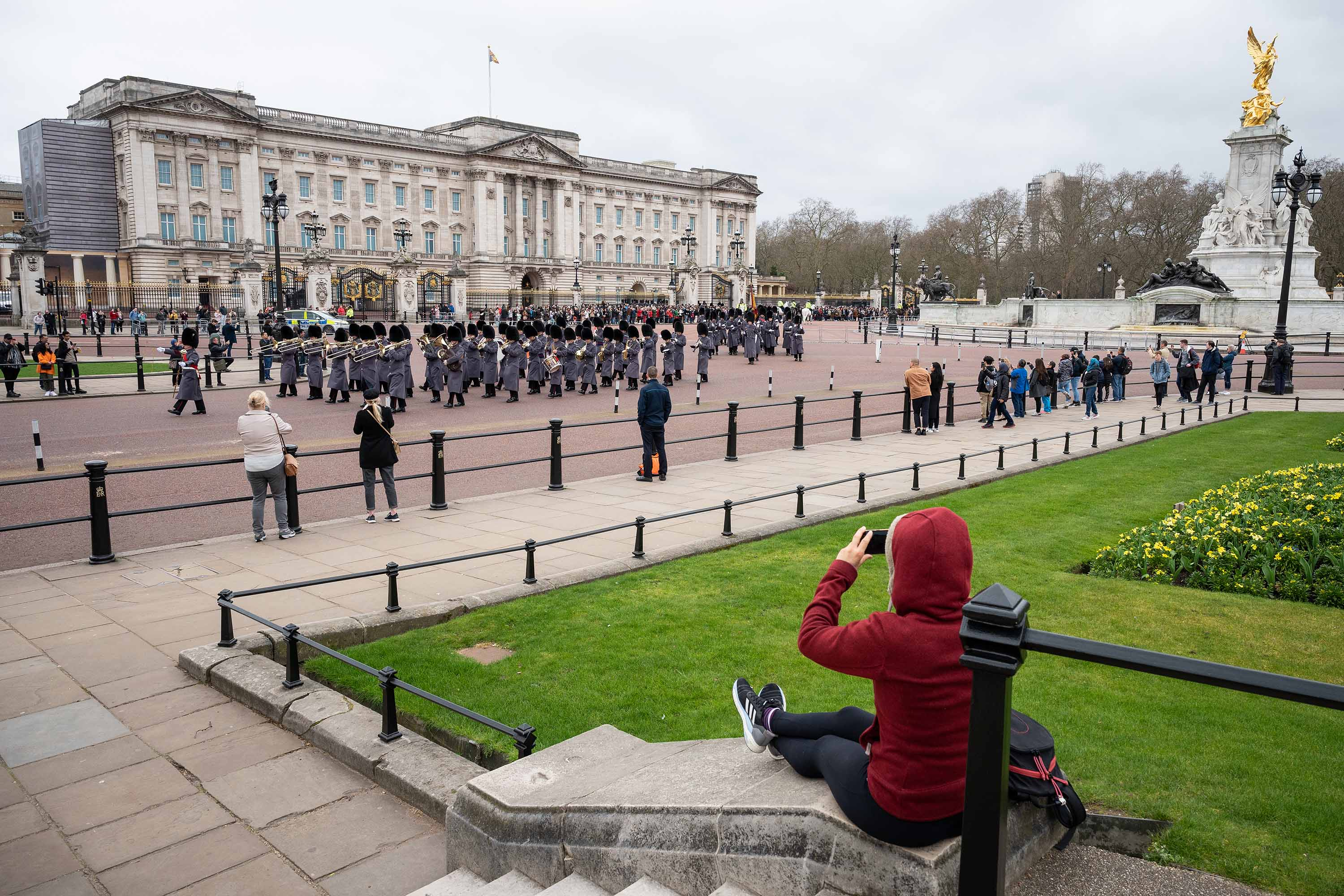 People watch the Changing of the Guard ceremony outside Buckingham Palace on March 18, in London, England.