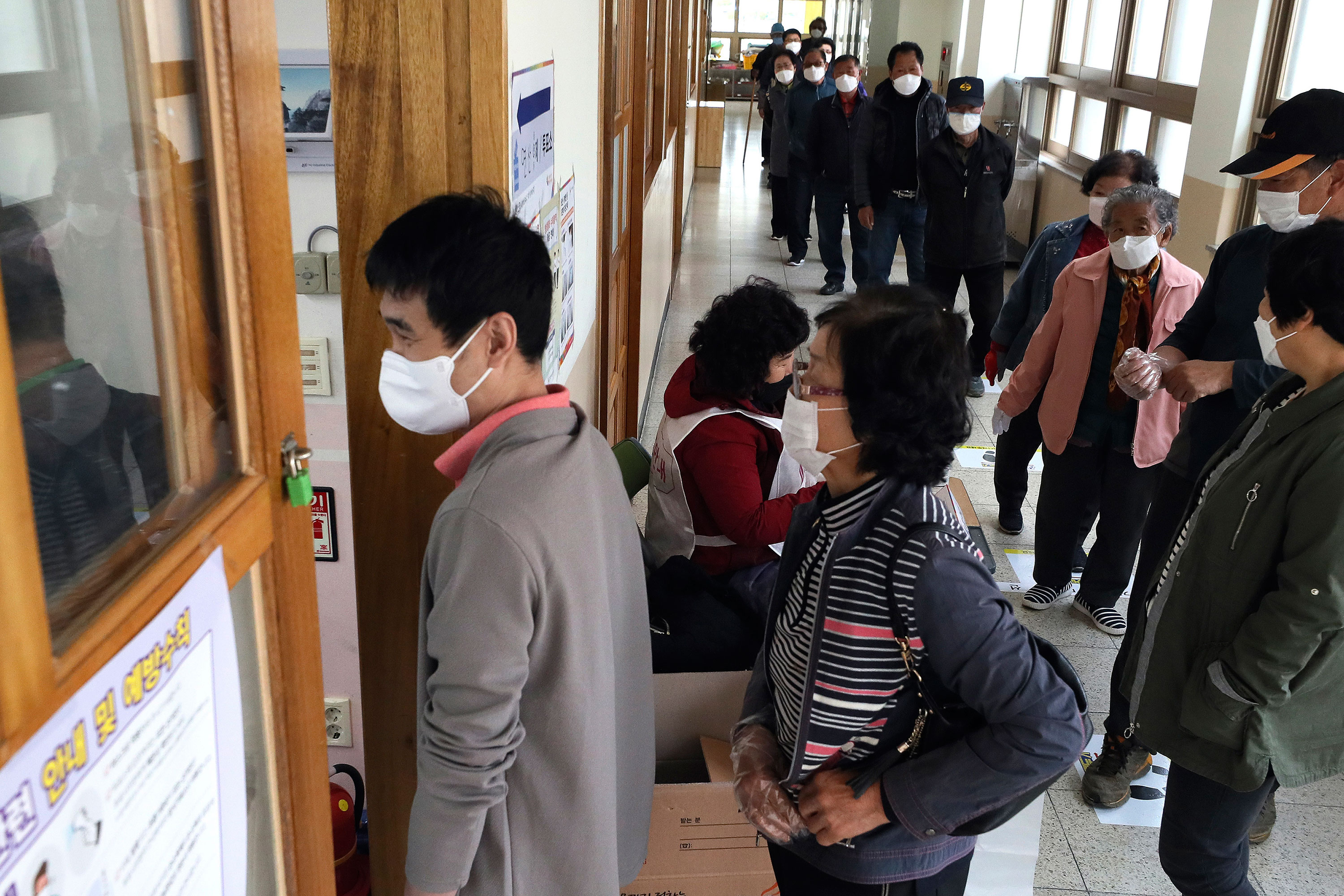 People wait in line to cast for their votes for the parliamentary elections at a polling station in Nonsan, South Korea, on April 15.