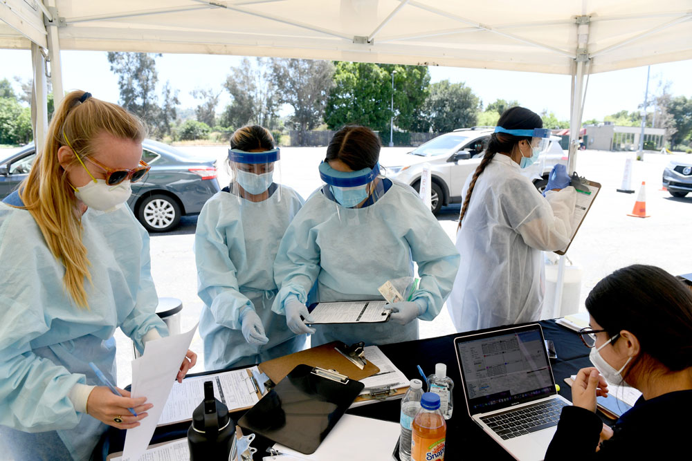 Workers wearing personal protective equipment perform drive-up Covid-19 tests at Mend Urgent Care testing site on May 13 in Los Angeles, California.