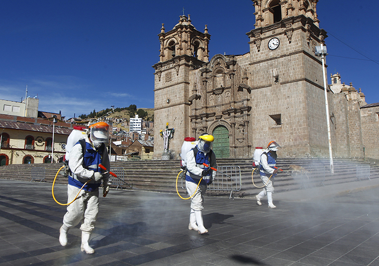 Health workers disinfect the main Plaza of Puno, Peru on June 18.