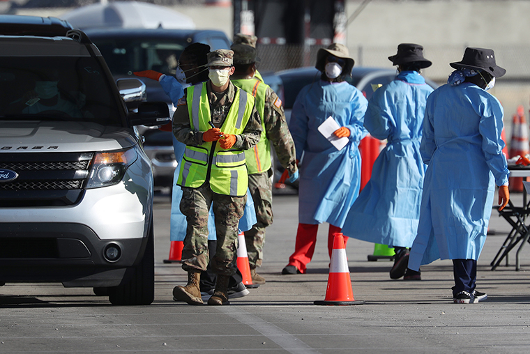 Health care workers check in people at a coronavirus testing site setup by the the Florida National Guard in the parking lot of the Hard Rock stadium on March 30, in Miami Gardens, Florida.