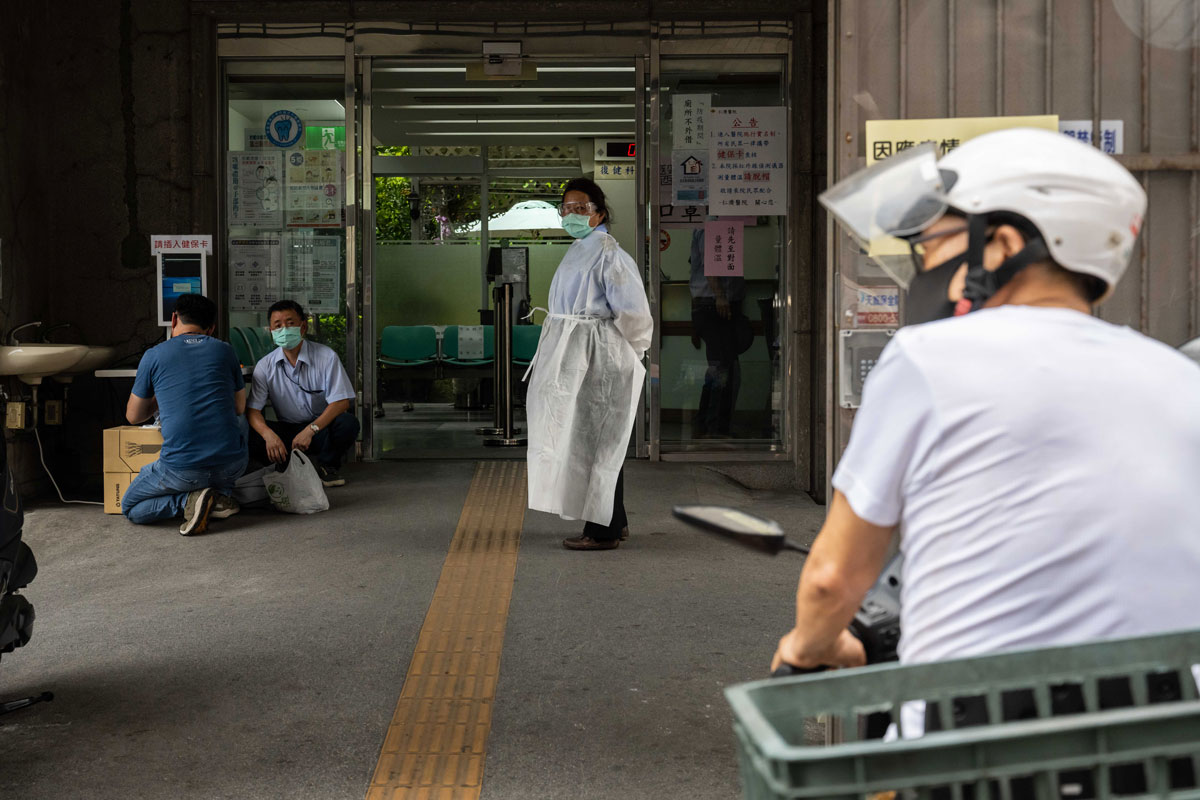 A worker wearing a protective mask and goggles stands in front of a hospital entrance in Taipei, Taiwan, on May 17.
