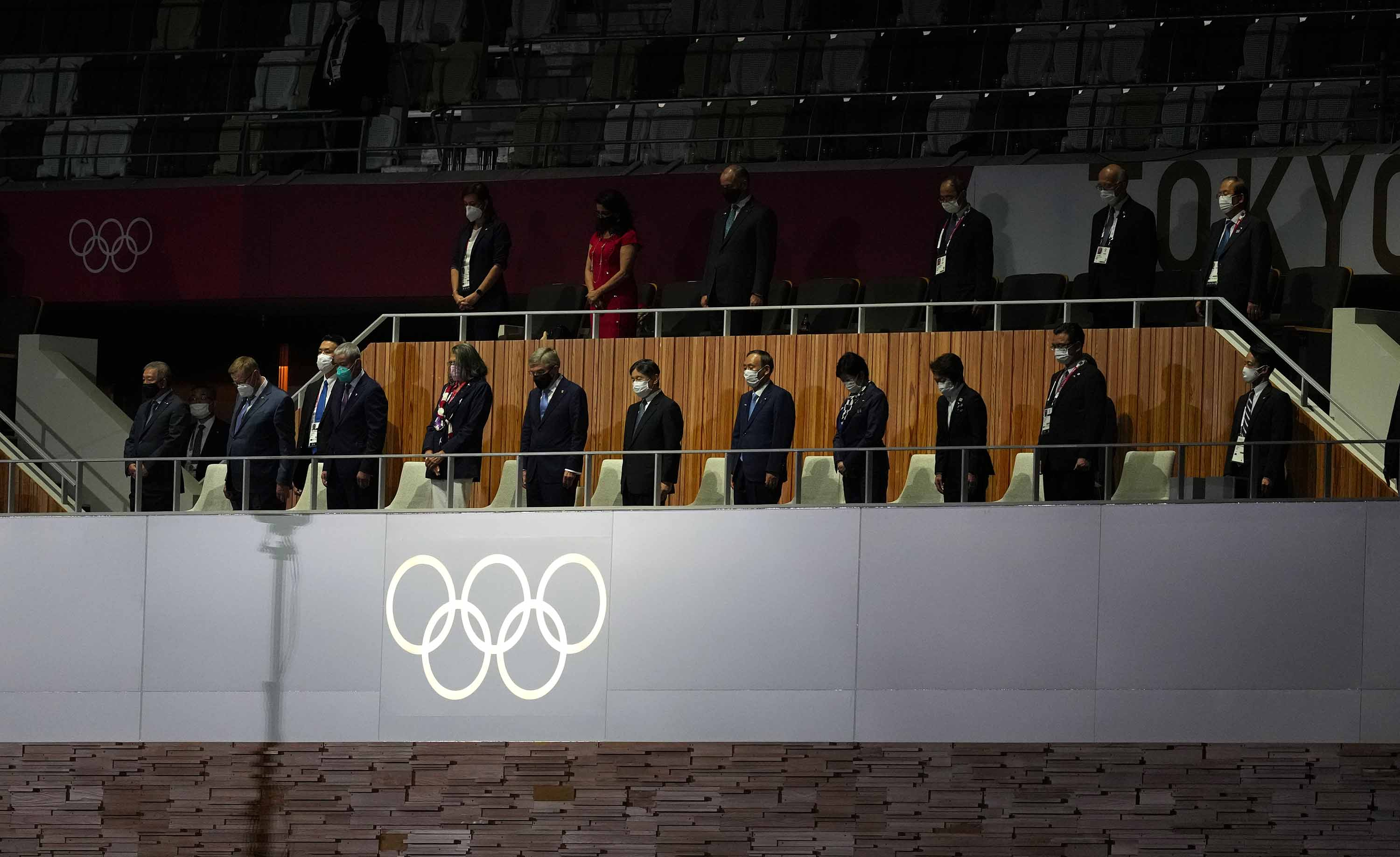 Japan's Emperor Naruhito, IOC president Thomas Bach and other delegates stand for a moments silence during the opening ceremony.