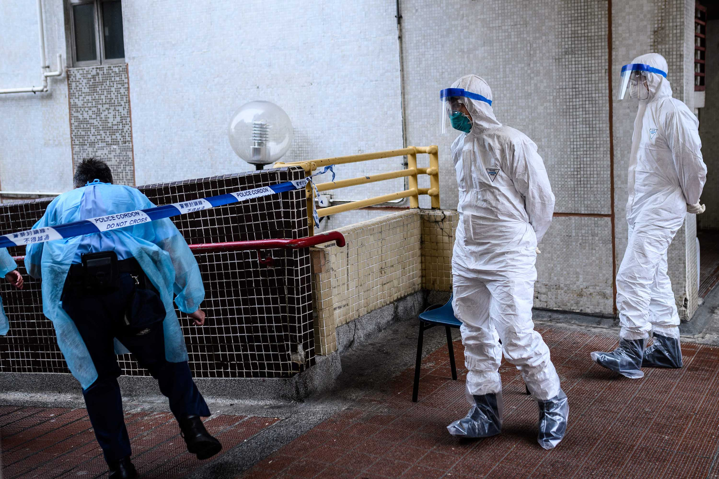 Police officers wearing protective gear are seen near a cordon outside Hong Mei House in Hong Kong on February 11, where some coronavirus cases were confirmed.
