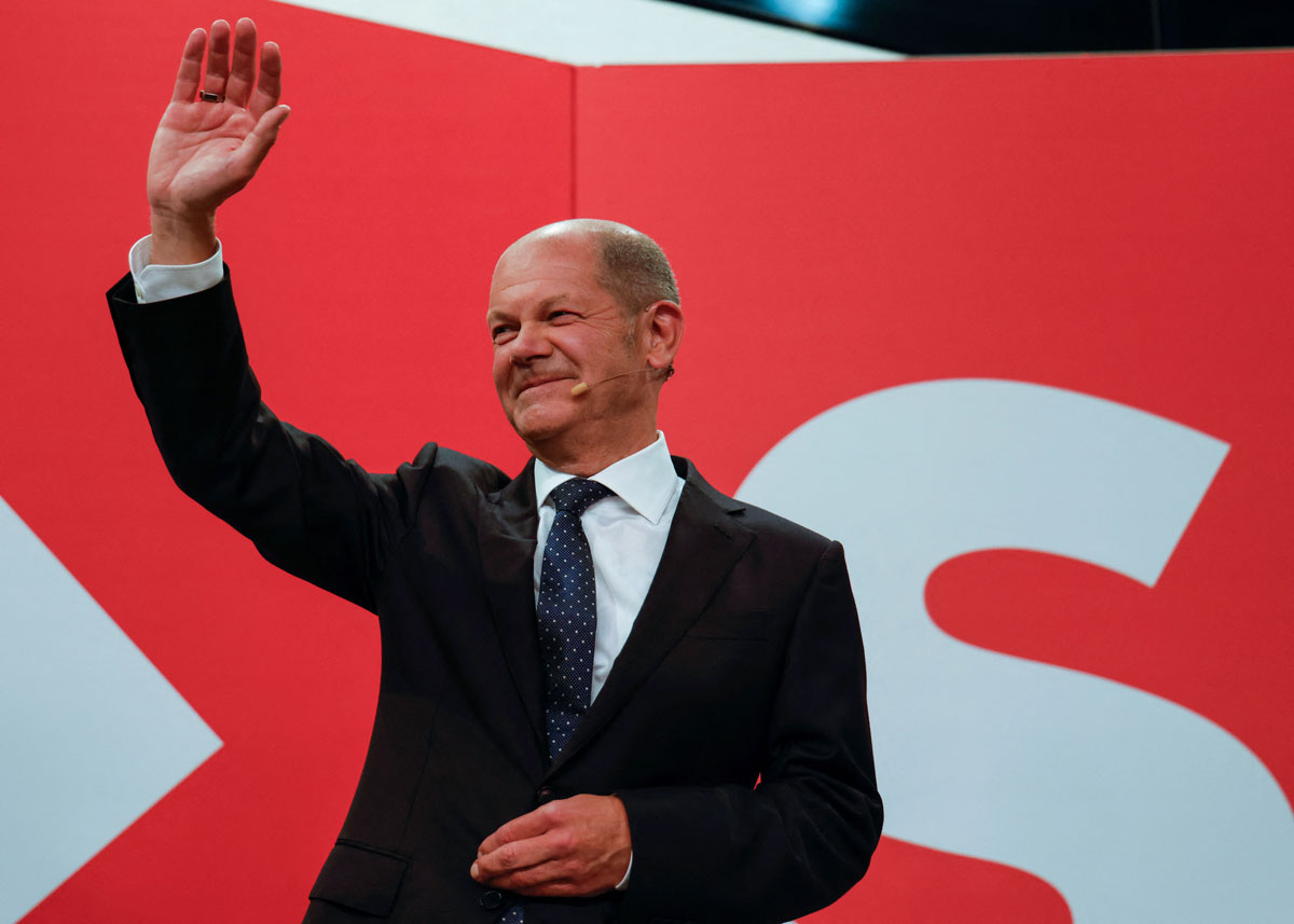 Olaf Scholzwaves at the Social Democrats headquarters after exit polls show the party's tight lead over the CDU.
