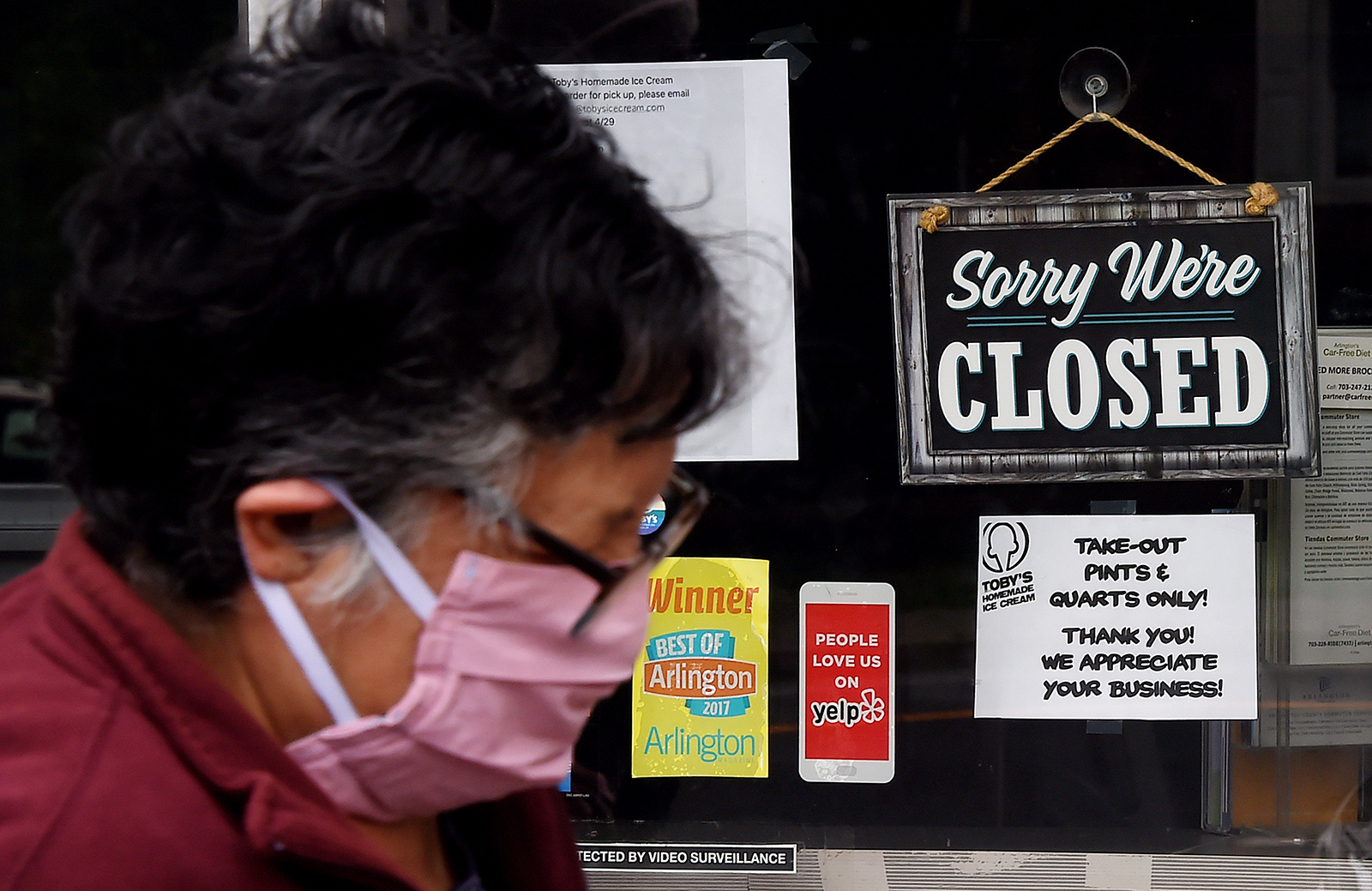 A person wearing a face mask walks past a sign in the window of an ice cream store in Arlington, Virginia on May 5.