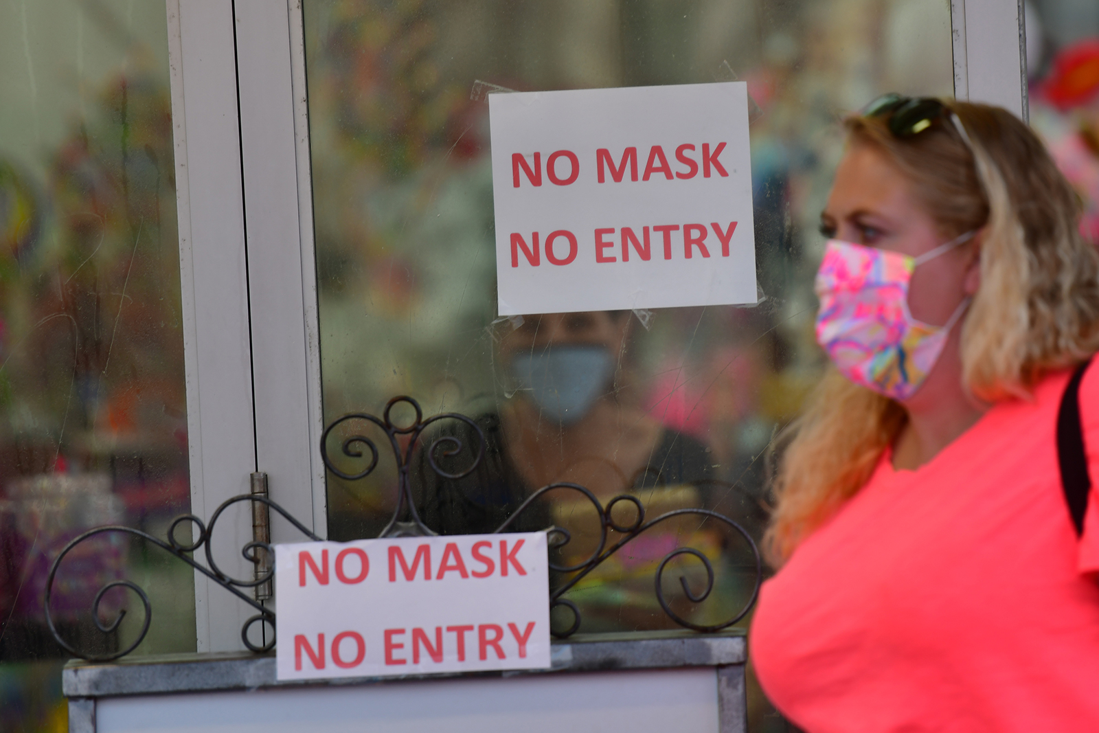 A woman wearing a face mask walks past a Boardwalk store with signs warning patrons of mask requirements on July 3, in Wildwood, New Jersey.