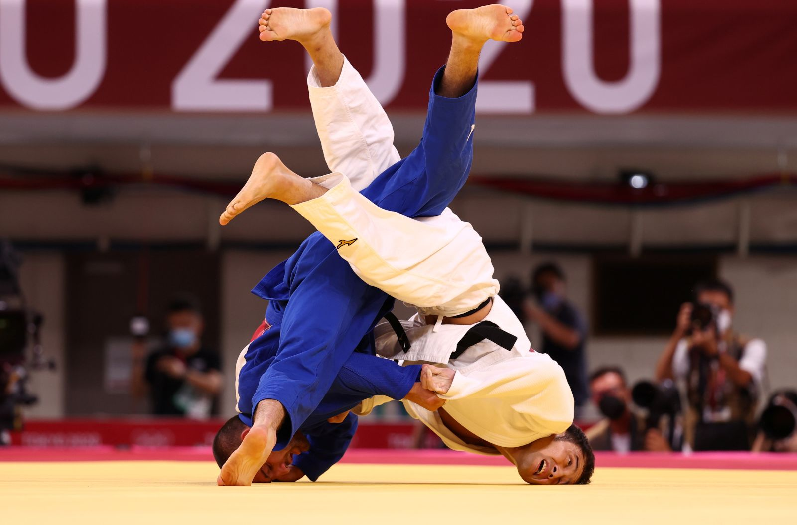 Japan's Naohisa Takato, in blue, competes against Georgia's Lukhumi Chkhvimiani in the men's 60kg judo quarterfinal on July 24. Takato went on to win the first gold medal for Japan, beating Yang Yung-wei of Chinese Taipei to clinch the men's 60kg judo title.