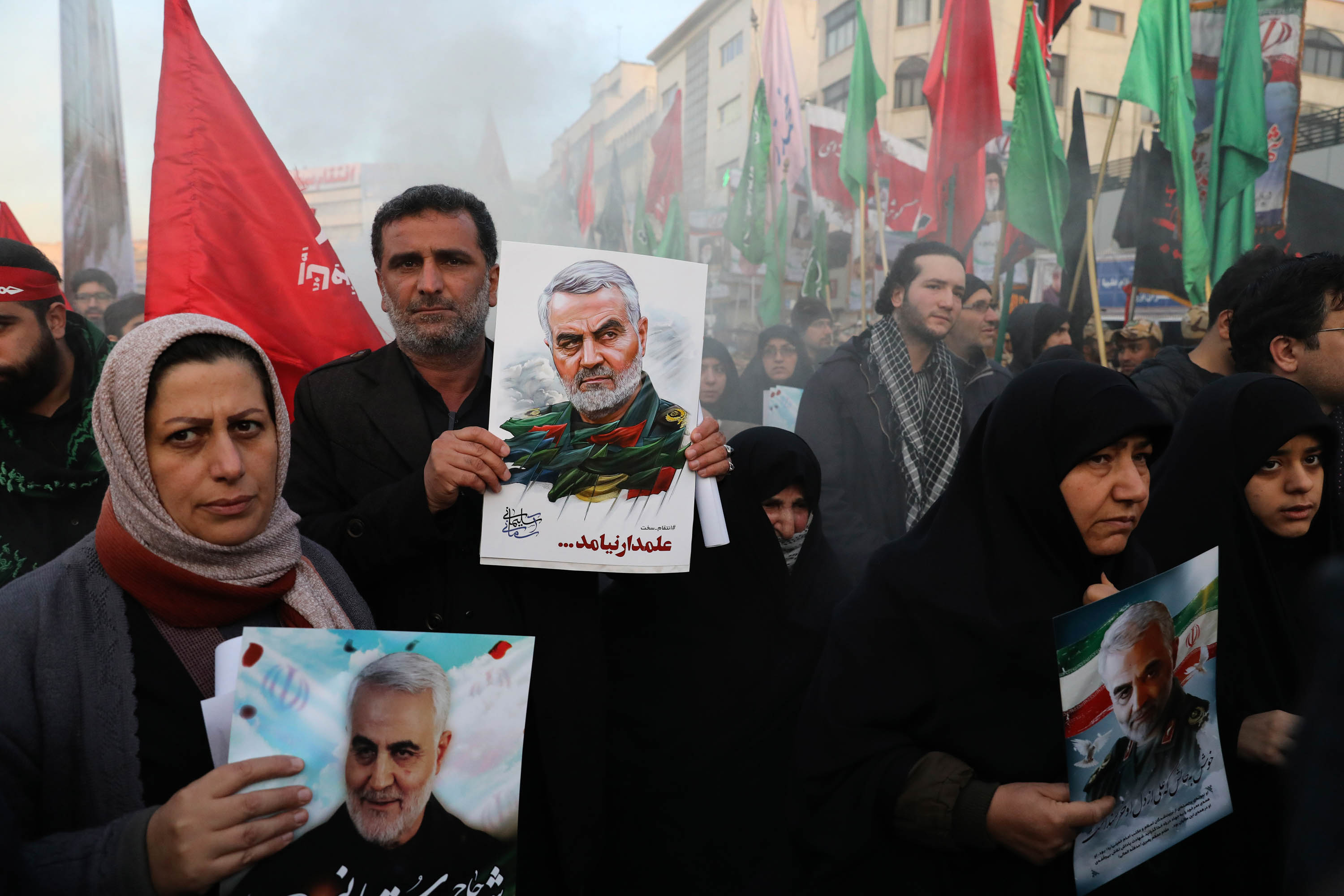 Mourners hold poster depicting Soleimani during his funeral ceremony in Tehran on Monday.