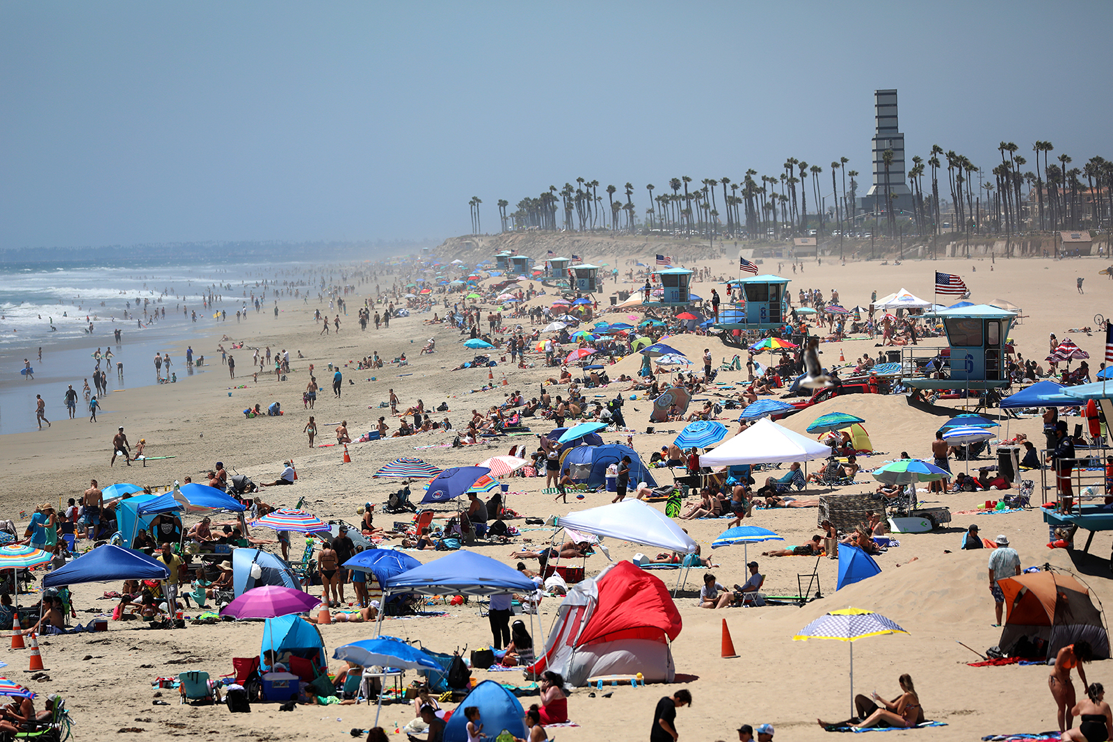 People gather at the beach on July 3, in Huntington Beach, California.