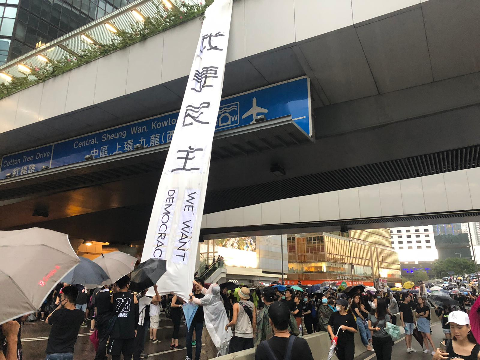 """Protesters unfurl a banner reading """"We want democracy"""" on Harcourt Road"""