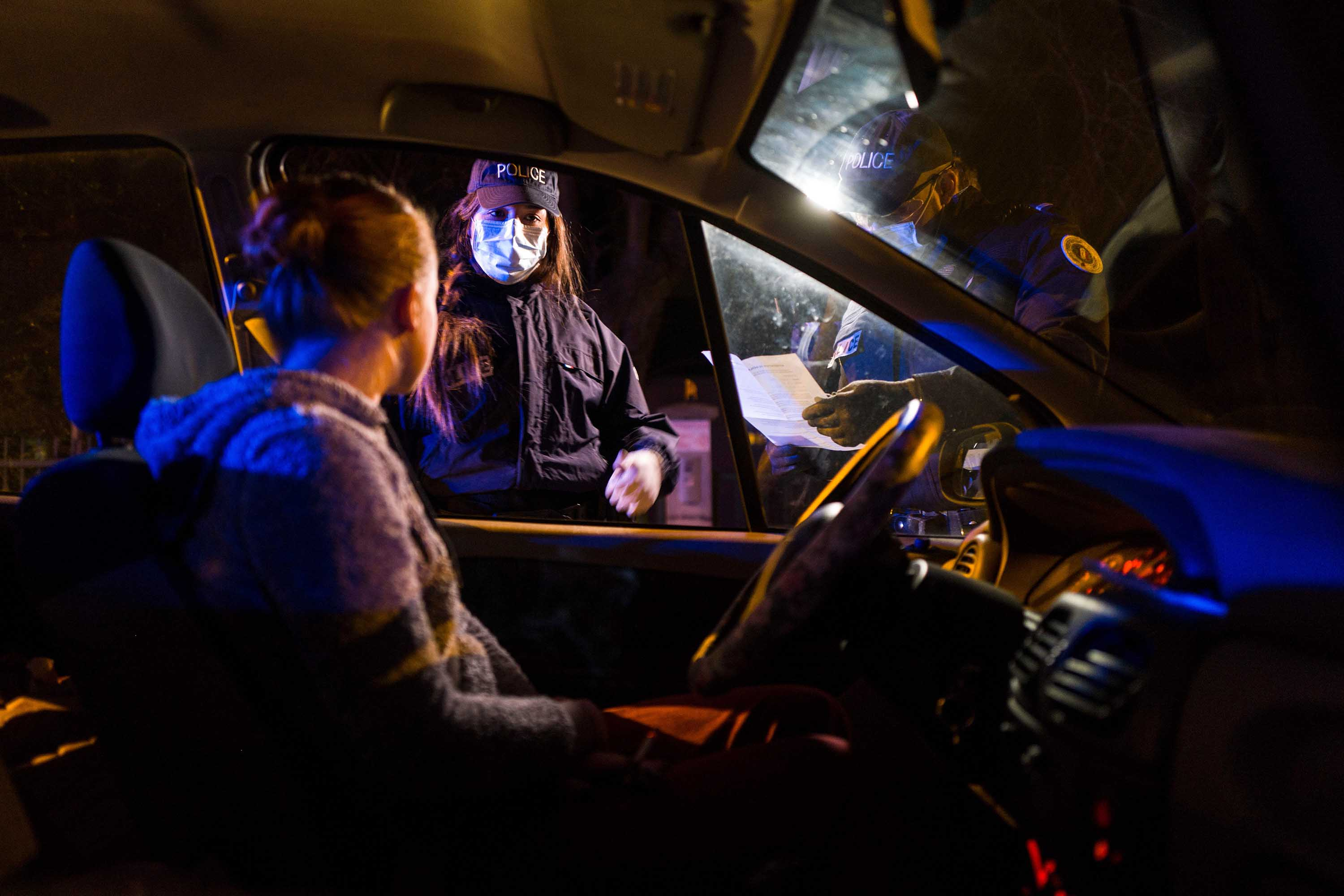 French police stop a motorist in Mulhouse, France, on March 31, to check they have a mobility form required by citizens to leave their homes during a curfew.