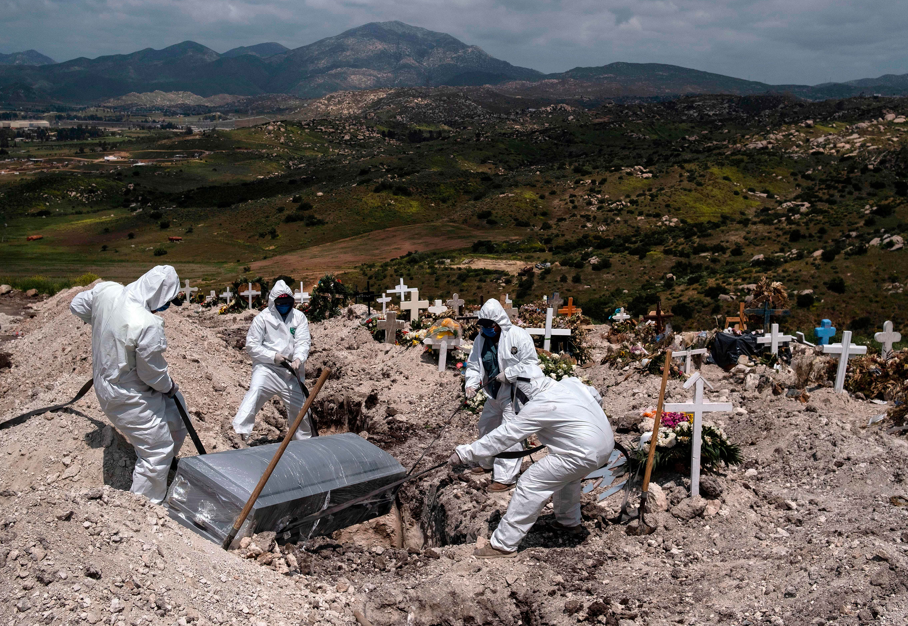 Cementery workers bury a coronavirus victim at a cemetery in Tijuana, Mexico, on April 21.