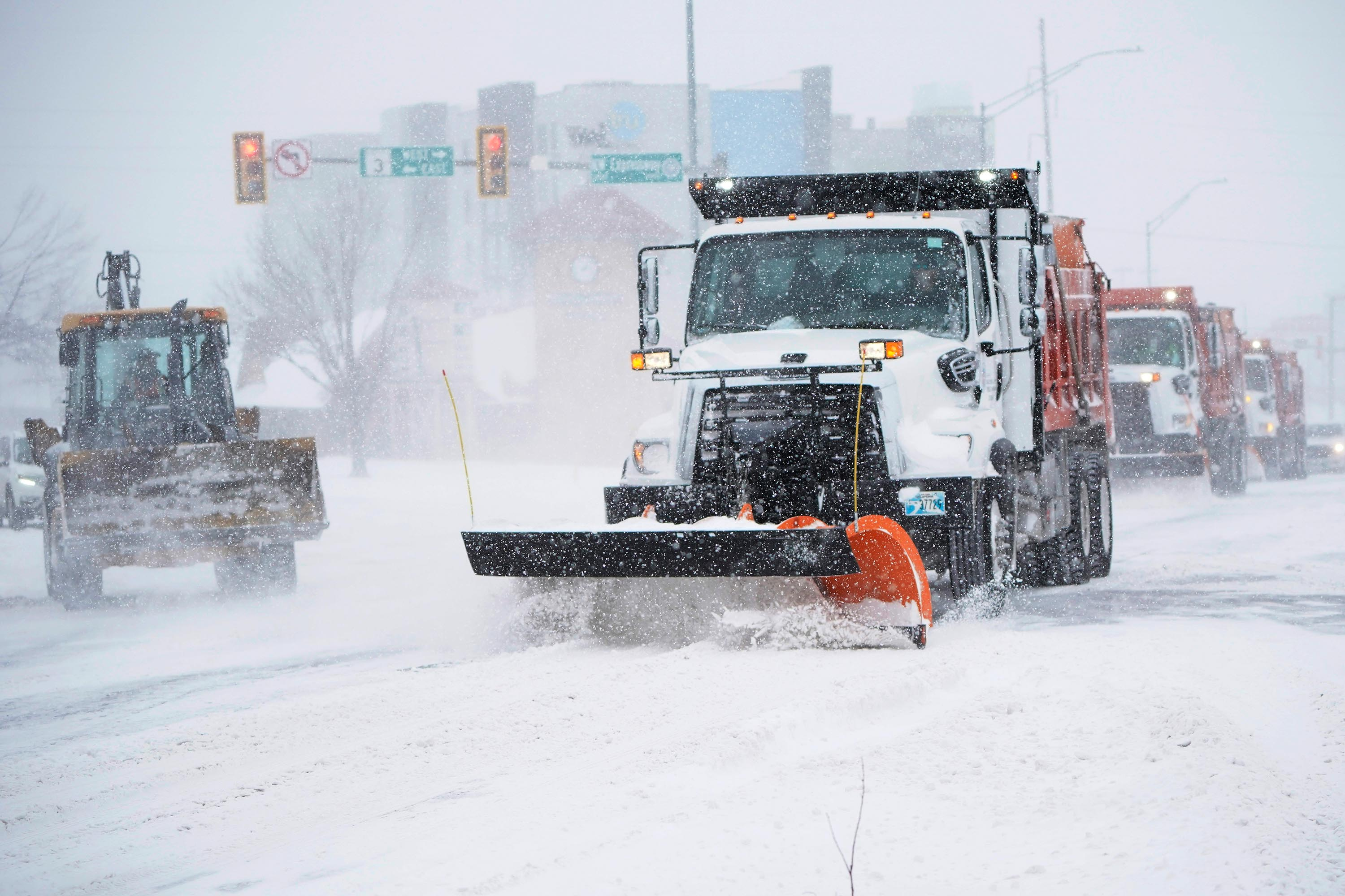 Vehicles work to clear an intersection during a winter storm Sunday, February 14, in Oklahoma City.