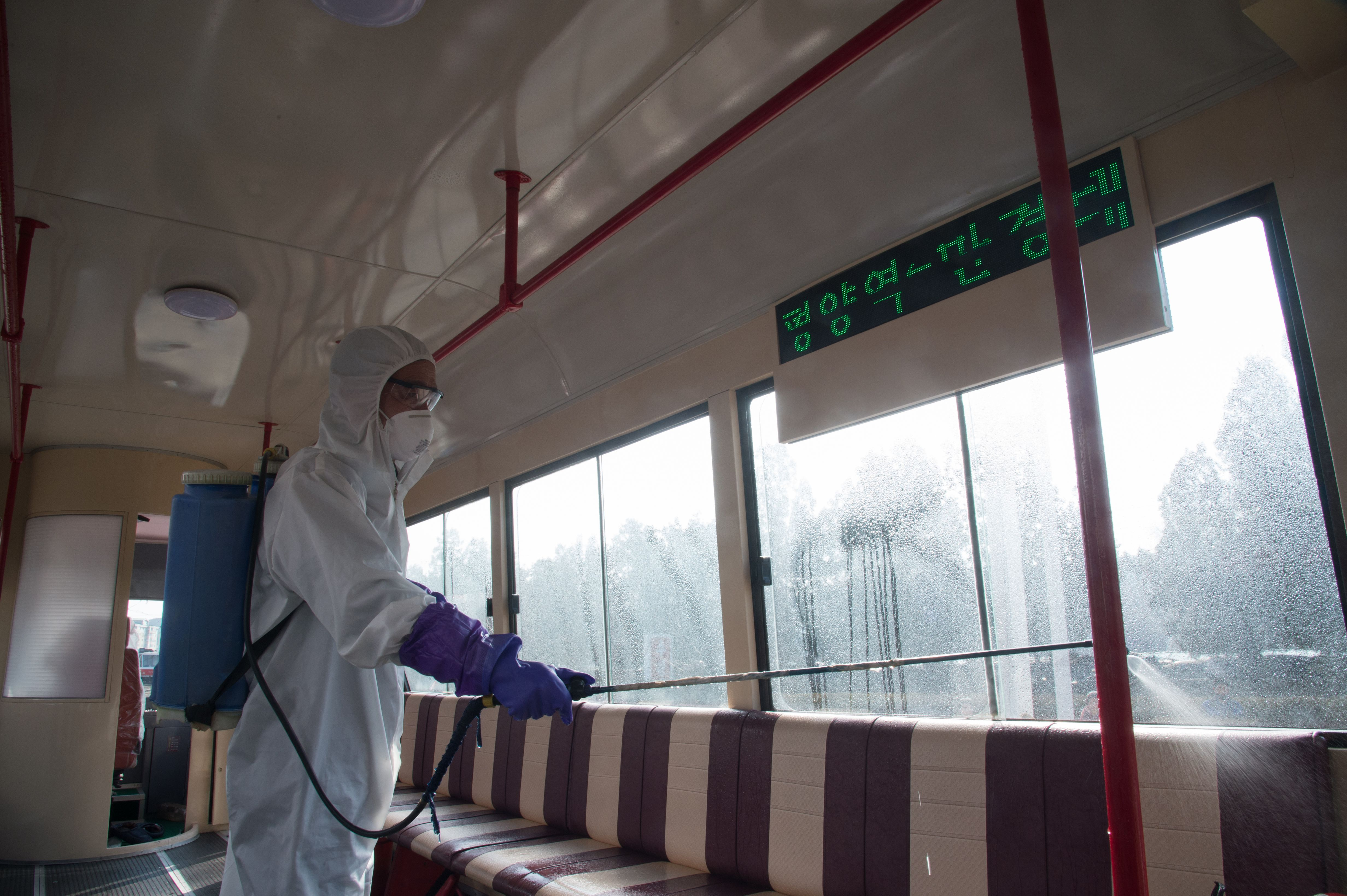 An official from the Mangyongdae District emergency anti-epidemic headquarters disinfects a tramcar at the Songsan Tram Station in Pyongyang.
