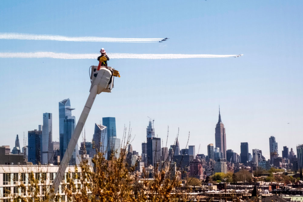 "A utility worker watches the US Navy's Blue Angels and the US Air Force's Thunderbirds conduct ""a collaborative salute"" to honor those battling the coronavirus pandemic with a flyover of New York and New Jersey, on Tuesday, April 28."