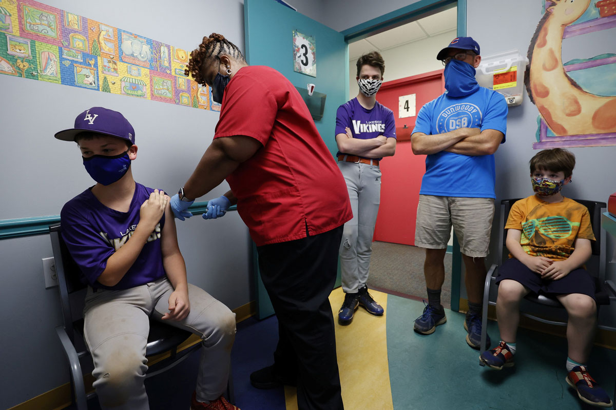 Family members look on as Jack Frilingos, 12, is inoculated with Pfizer's vaccine against Covid-19 after Georgia authorized the vaccine for ages 12 and up, at Dekalb Pediatric Center in Decatur, Georgia on on May 11.