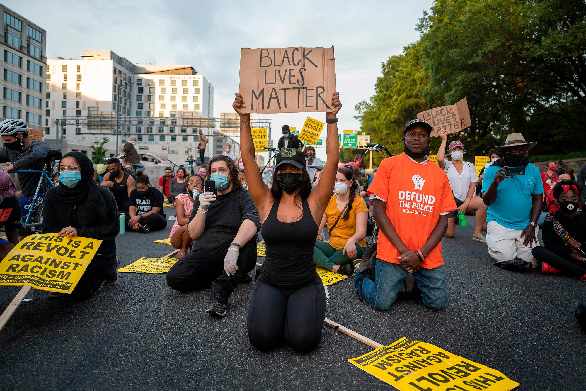 Protesters kneel and hold up signs as they demonstrate the death of George Floyd by blocking traffic on I-395 in Washington on June 15.