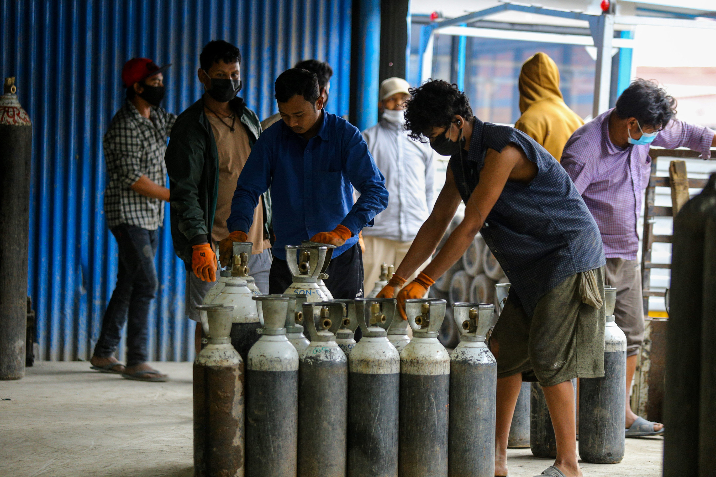 Workers unload oxygen cylinders at a hospital in Lalitpur, Nepal, on May 2.
