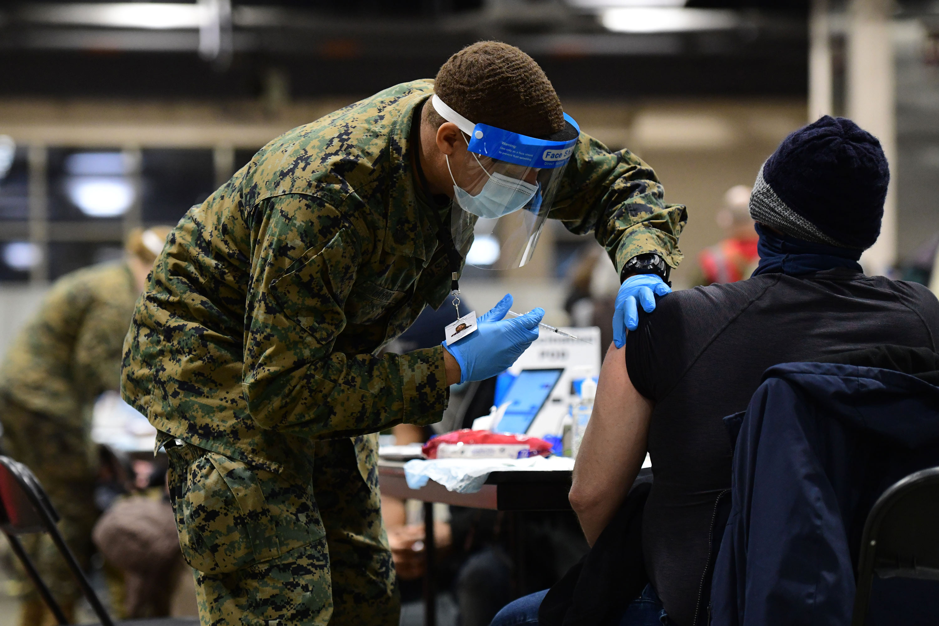 A member of the U.S. Armed Forces administers a dose of the Pfizer COVID-19 vaccine at a FEMA community vaccination center on March 2 in Philadelphia, Pennsylvania.