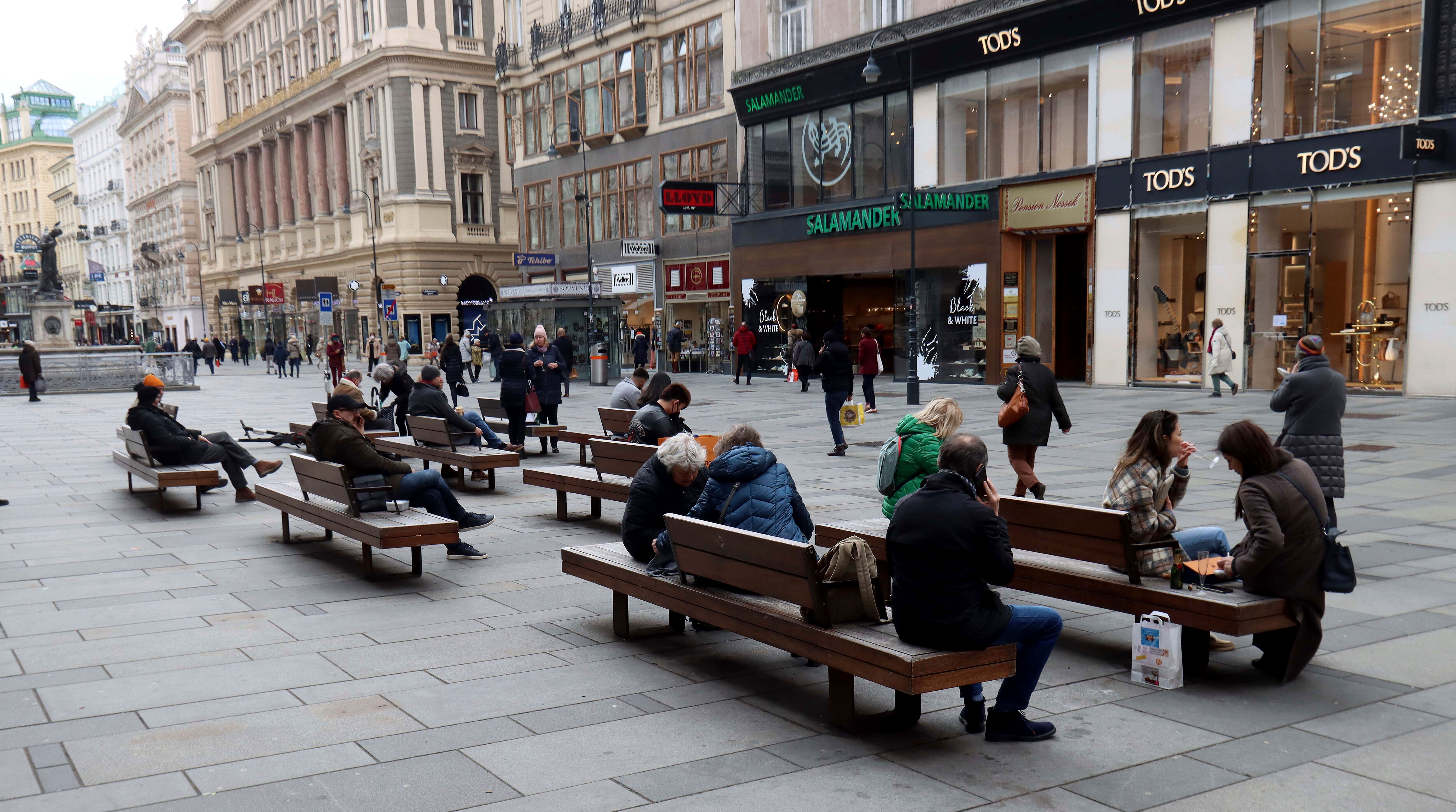 People sit on benches in downtown Vienna, Austria, on March 22.