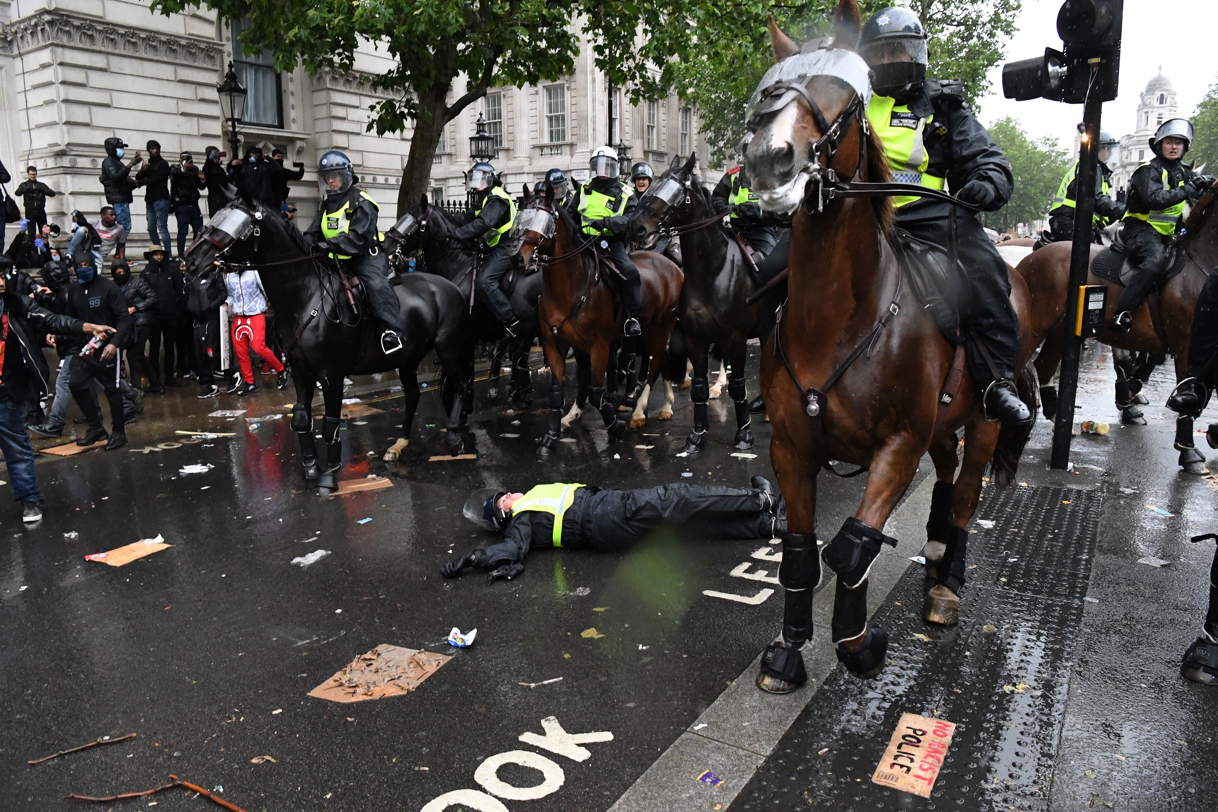 A police officer lies on the ground after her horse bolted.