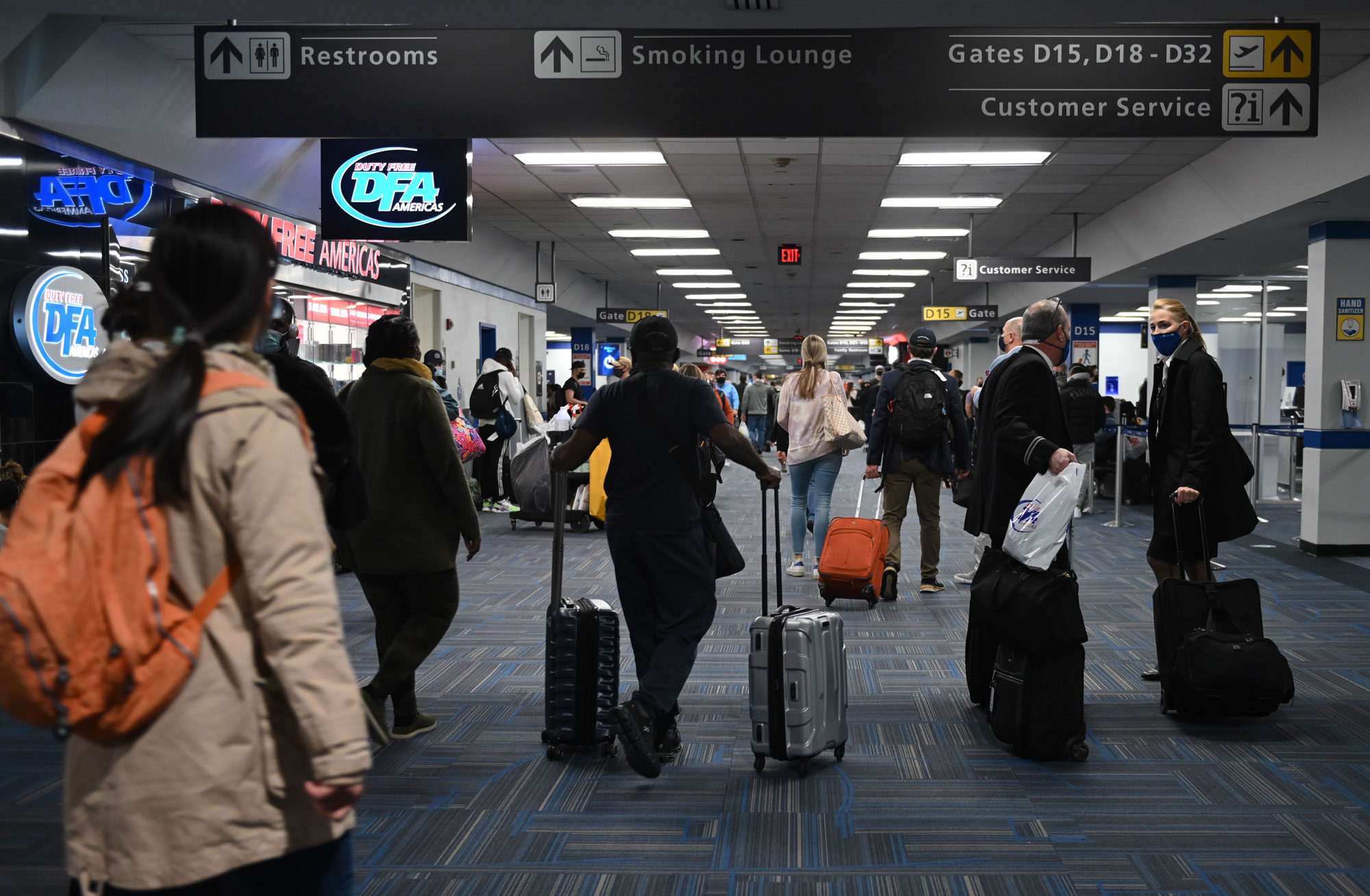 Passengers walk through a terminal at Dulles International airport in Dulles, Virginia on December 27, 2020.