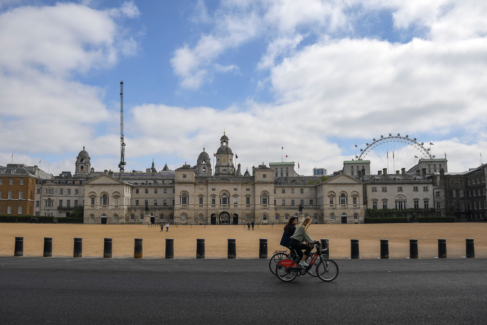 Two women ride bicycles past the Horse Guards Parade, during lockdown due to the coronavirus outbreak, in London, on Saturday, April 25.
