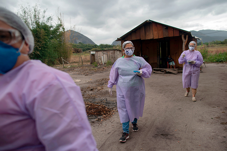 Health professionals leave a home after administering COVID-19 tests to an elderly indigenous Guarani couple at the Sao Mata Verde Bonita tribe camp, in Marica, Rio de Janeiro state, Brazil, on July 2.