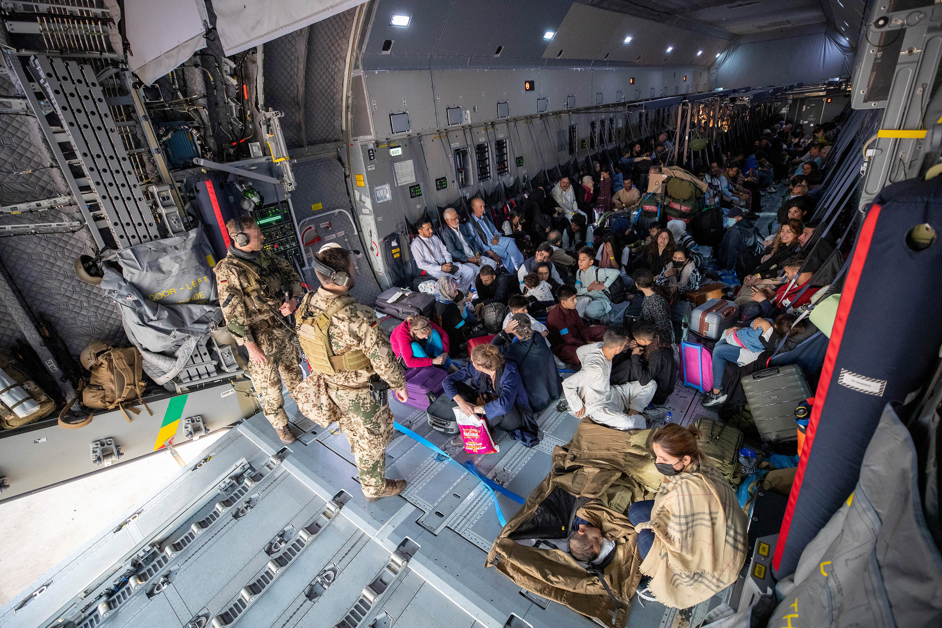 Evacuees from Kabul sit inside a military aircraft in Tashkent, Uzbekistan, on August 17, before reaching their final destination in Germany.