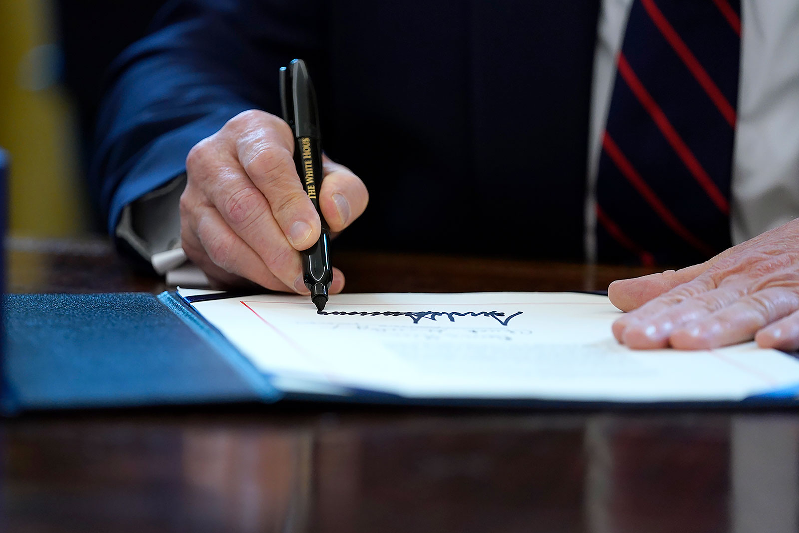 President Trump signs the coronavirus stimulus relief package in the Oval Office at the White House on Friday, March 27.