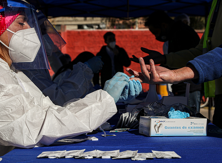 Healthcare workers conduct rapid COVID-19 tests at a testing site geared for garbage collectors street-sweepers and street vendors, at a sports center in Santiago, Chile, Wednesday, July 15.