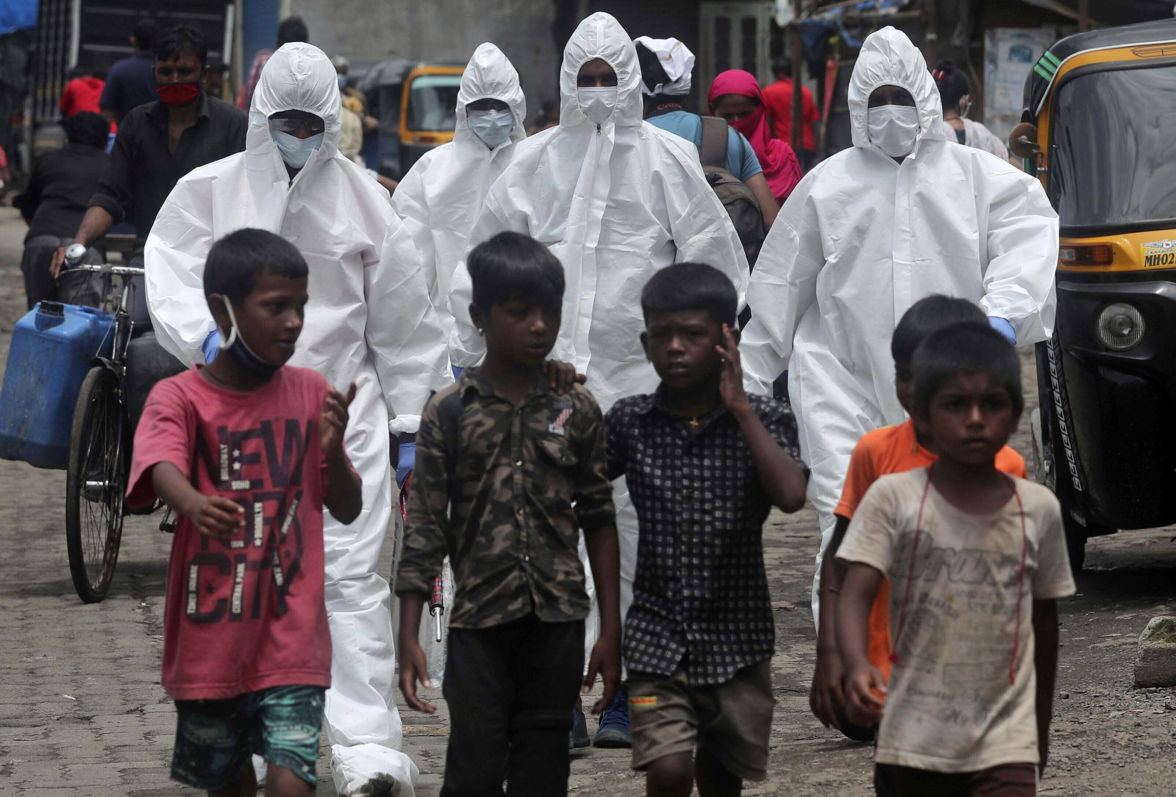 Health workers wearing protective clothing arrive to screen people for Covid-19 symptoms at a slum in Mumbai on Friday.