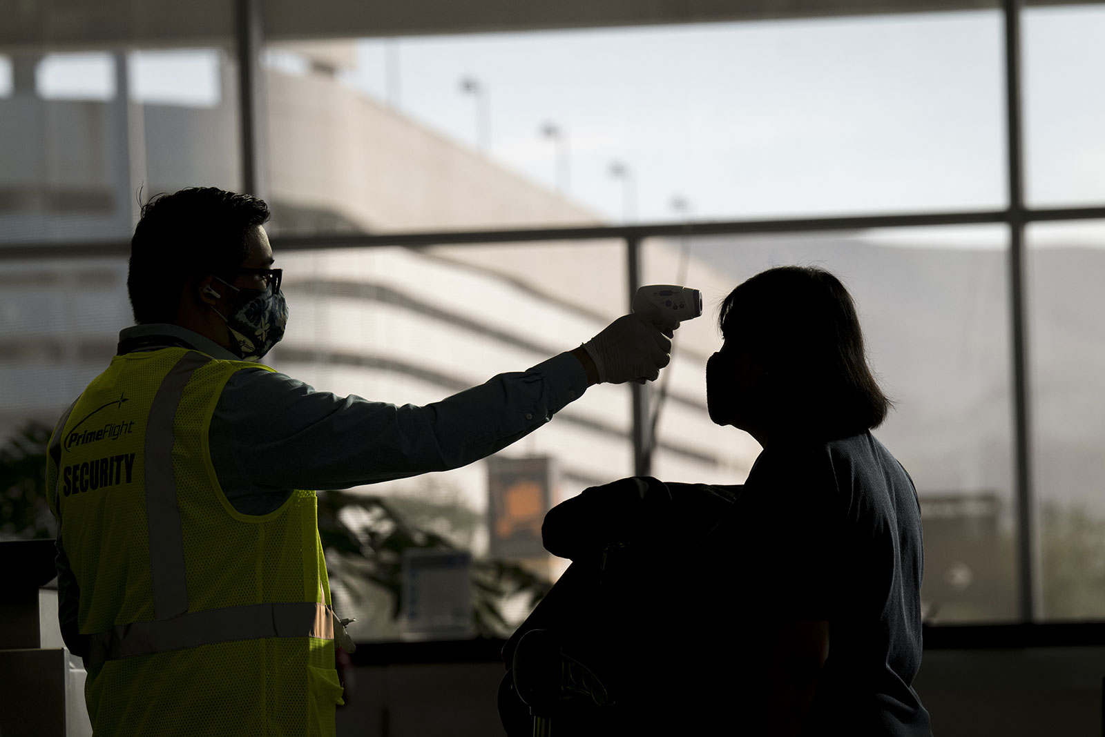 An airport employee measures the temperature of a traveler at San Francisco International Airport on Monday, June 1.