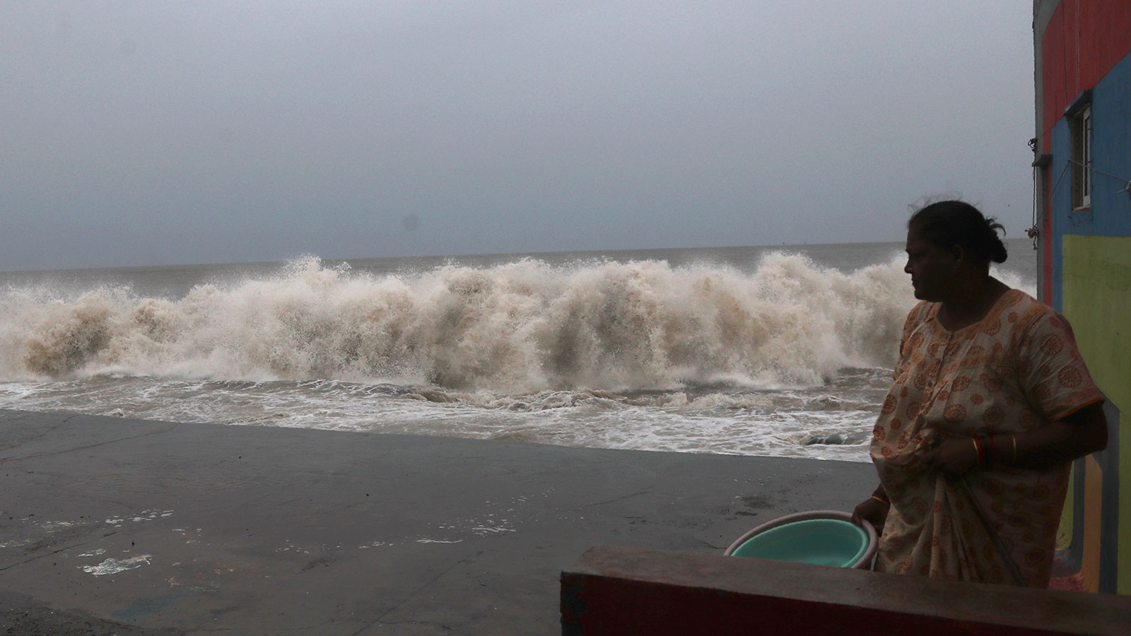 A woman watches waves splash on shores of the Arabian Sea in Mumbai, India on June 3.