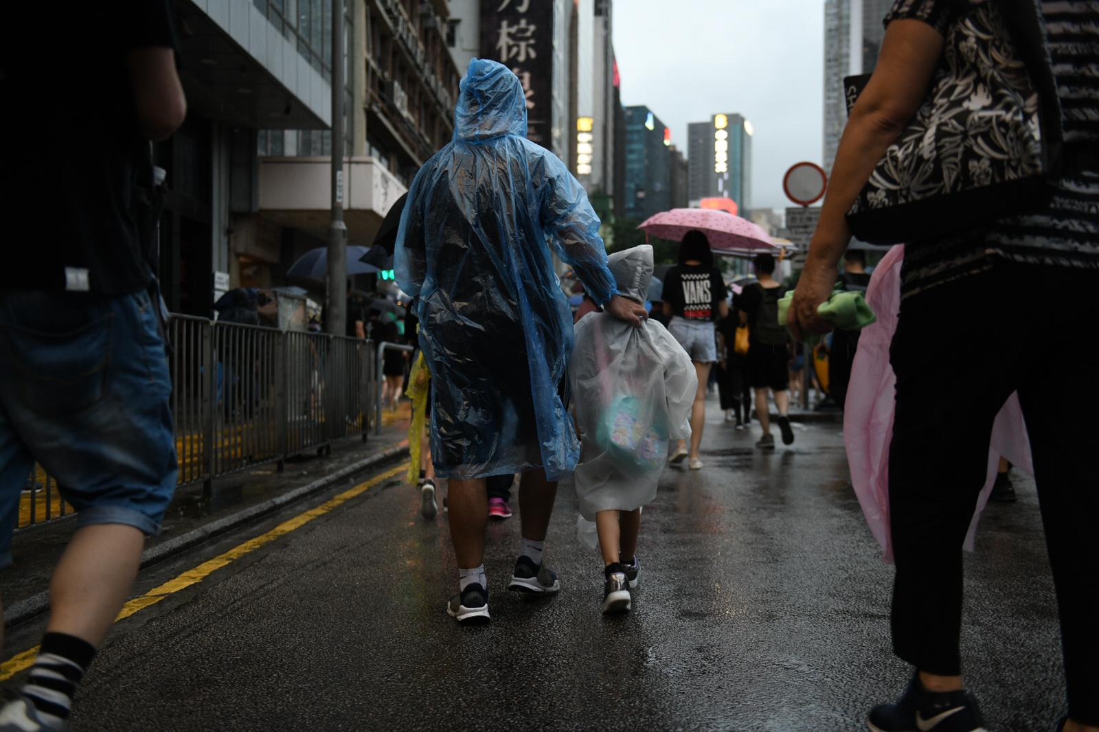 A family marches on in the rain.