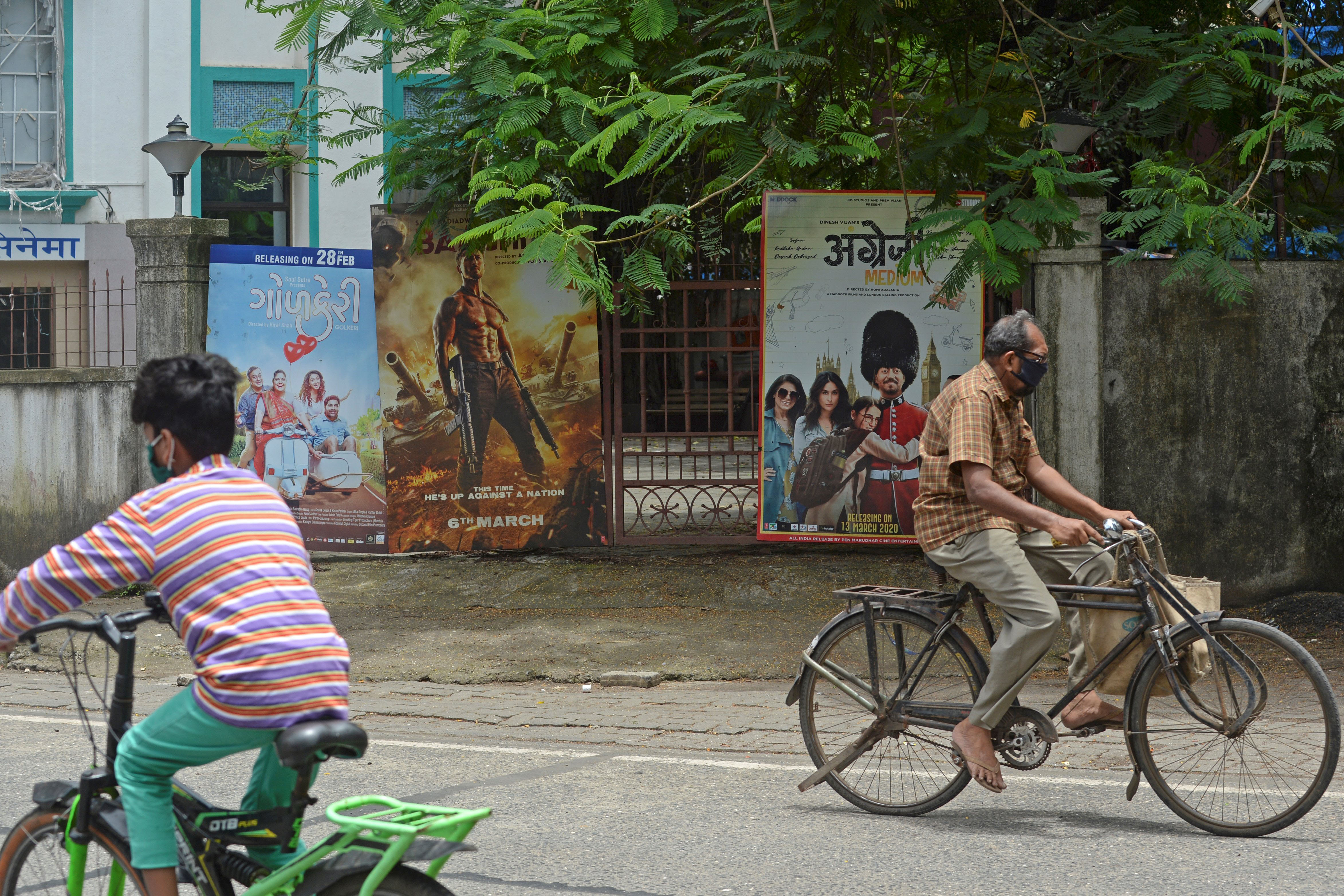 People bike past a closed movie theater in Mumbai, India, on July 21.