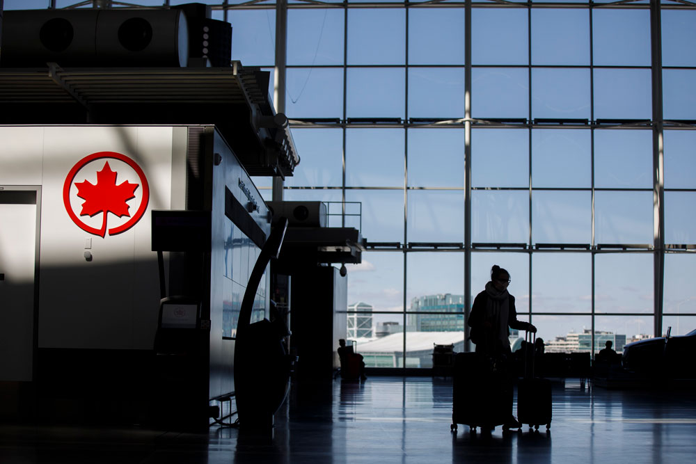 A passenger wheels her luggage near an Air Canada logo at Toronto Pearson International Airport on April 1 in Toronto, Canada.