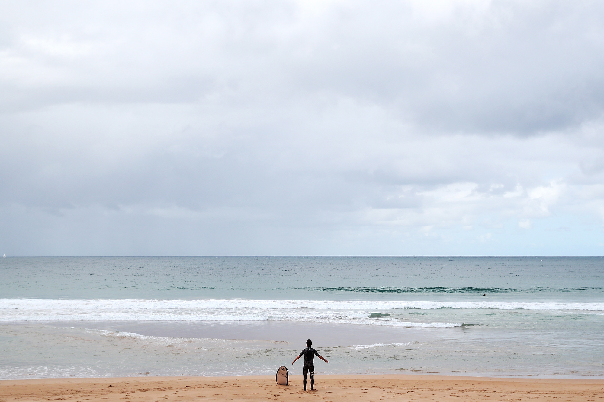 A surfer is seen on Manly Beach as the majority of residents and tourists follow the government's advice to self-isolate on March 23 in Sydney, Australia.
